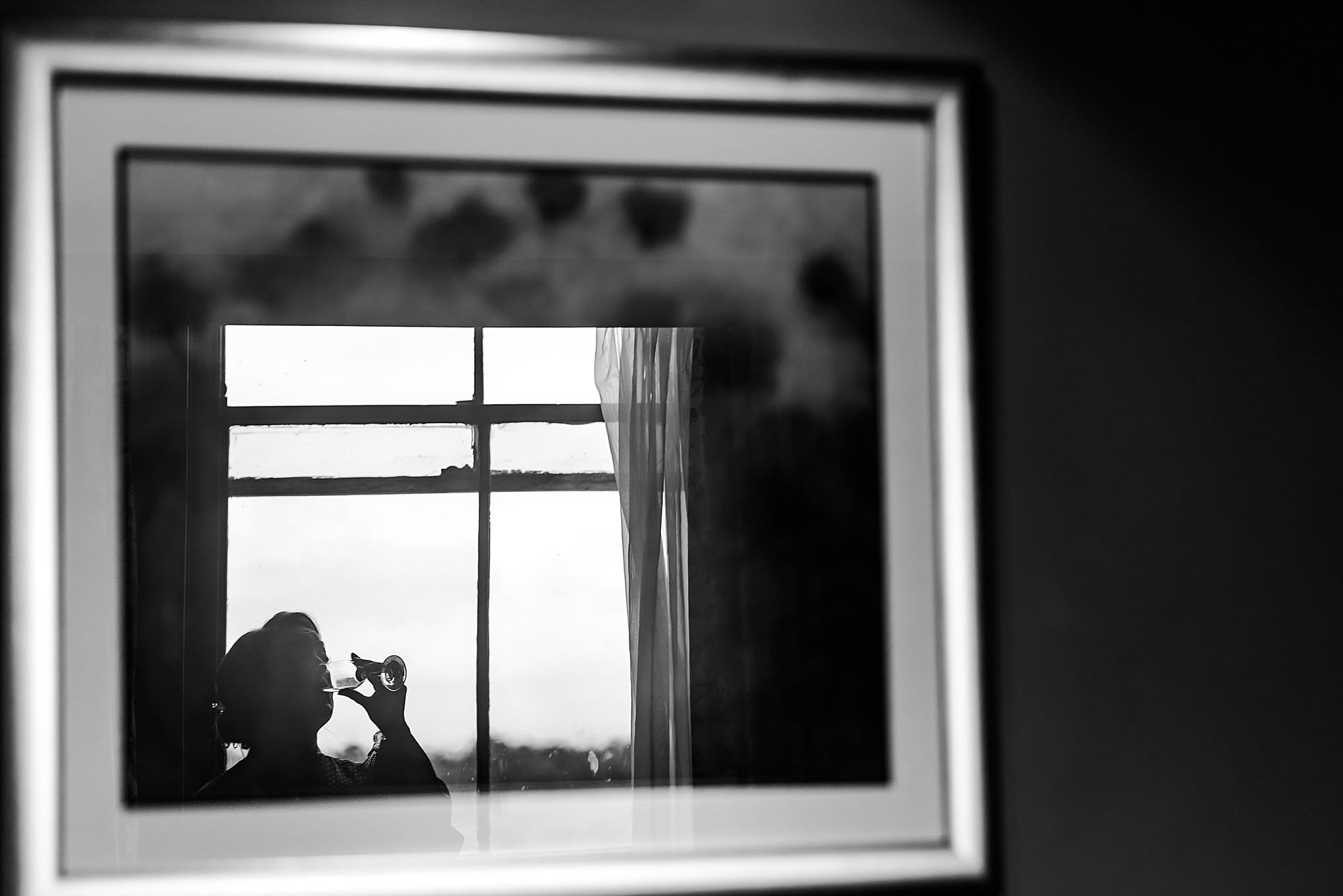 Silhouette of bride having a drink reflected in a picture frame