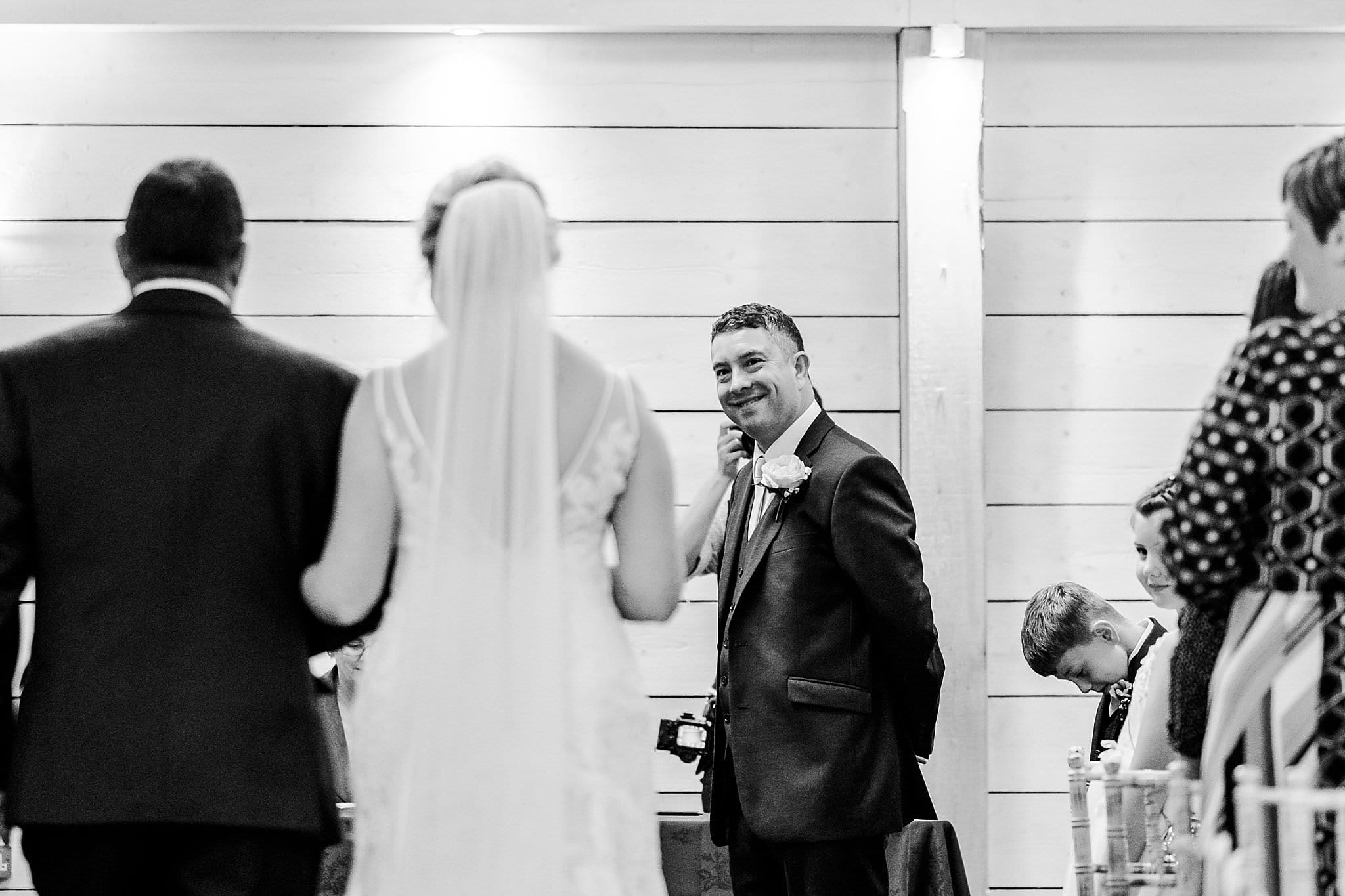 Groom looks back up the aisle as bride and her father walk towards him at Newton House Barns