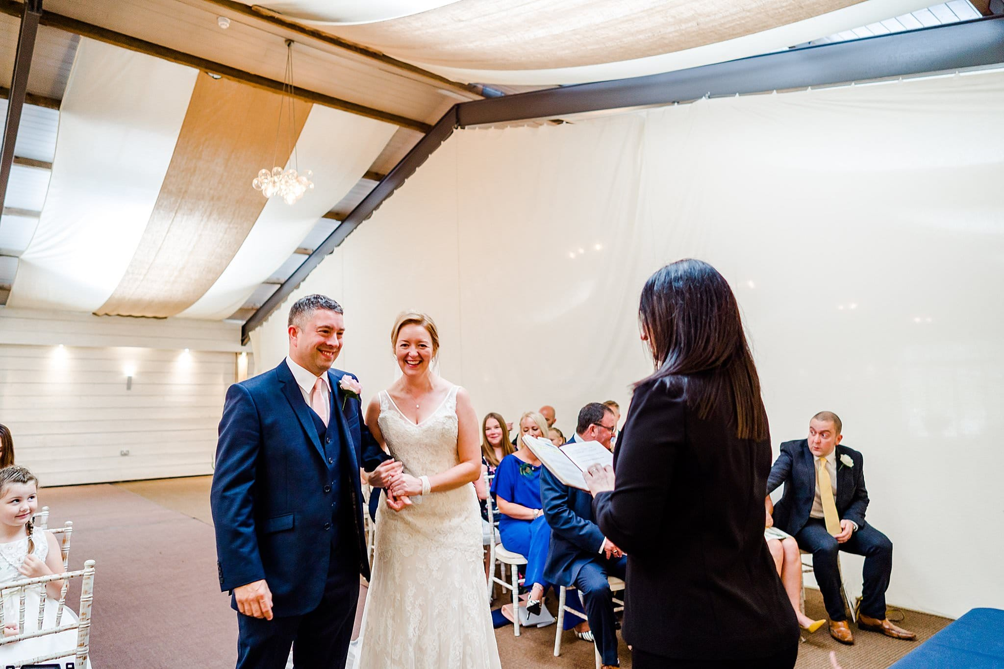 Bride and groom look nervous during their wedding ceremony at Newton House Barns