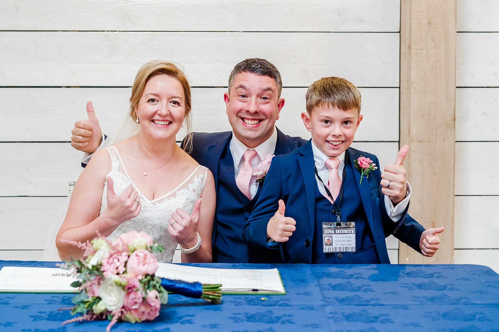 Bride, groom and their son all have thumbs up after their wedding ceremony at Newton House Barns