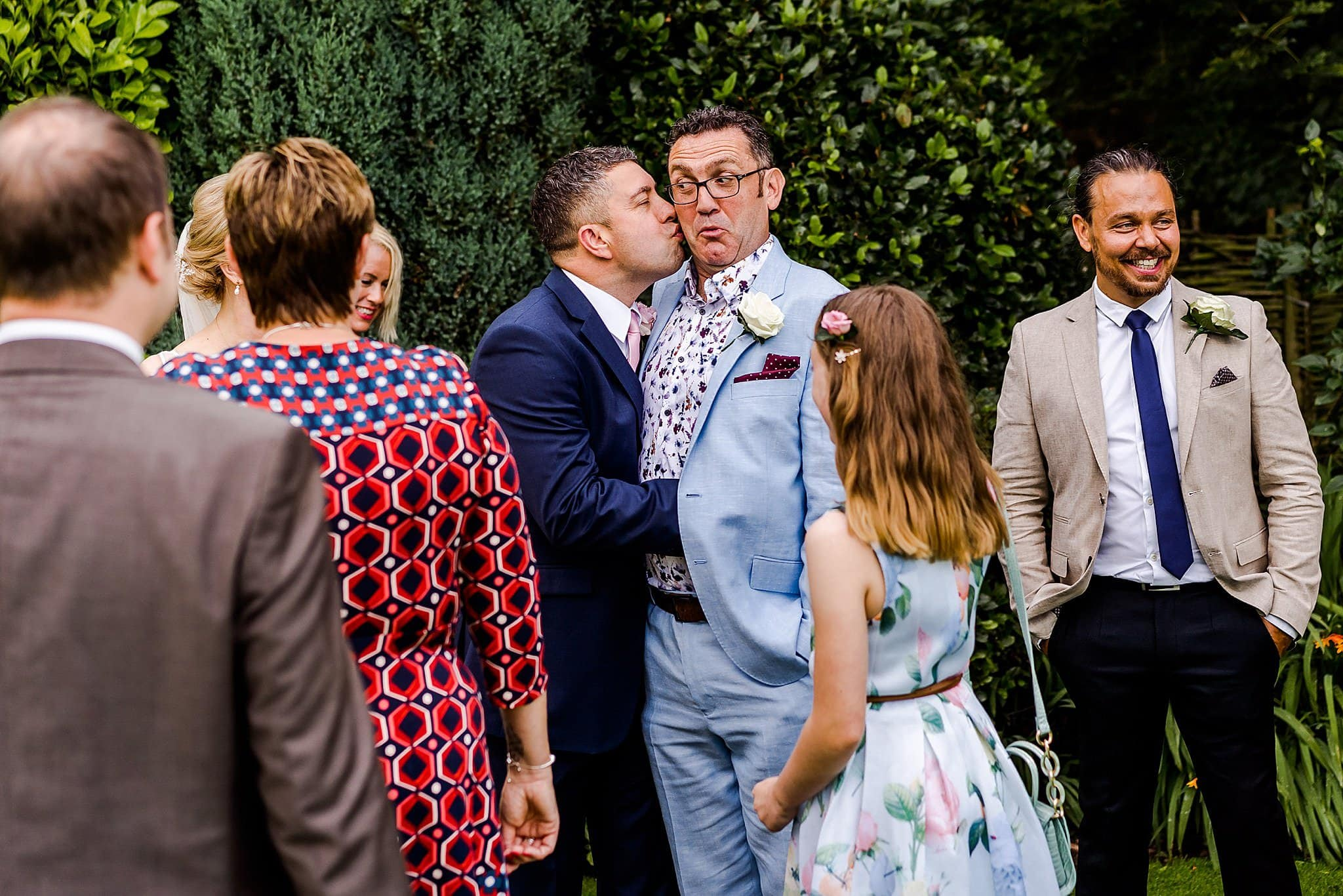 Candid photo of groom kissing a wedding guest and others laughing at Newton House Barns