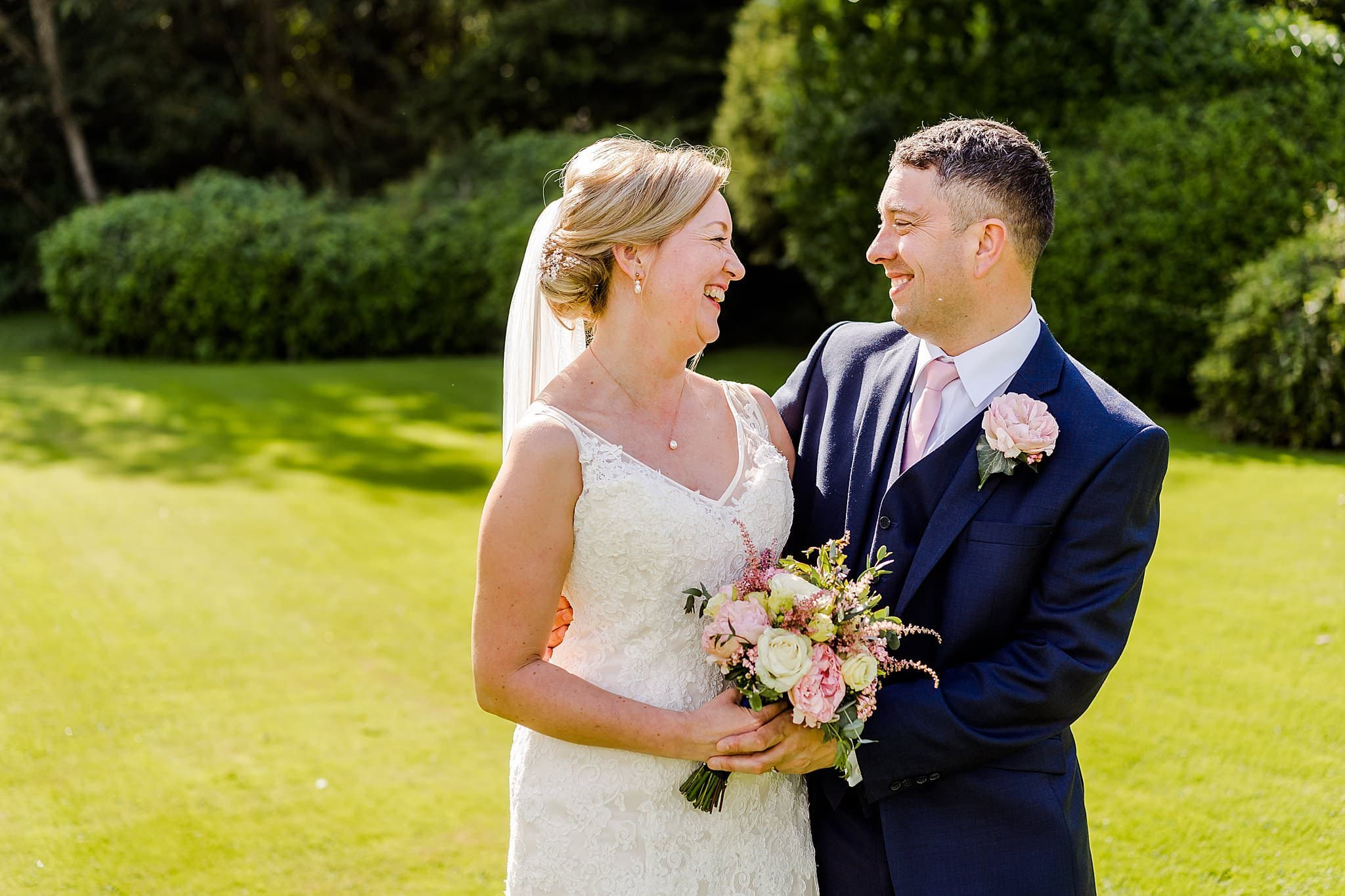 Bride and groom smile at each other during their bridal couple's shoot at Newton House Barns