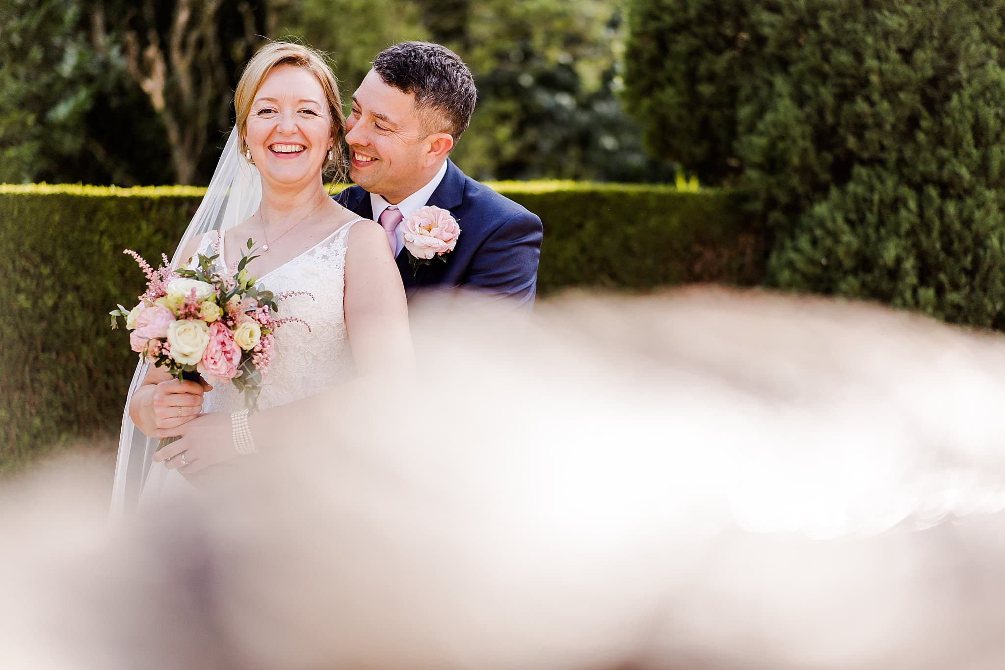 Groom smiles at bride whilst hugging at Newton House Barns