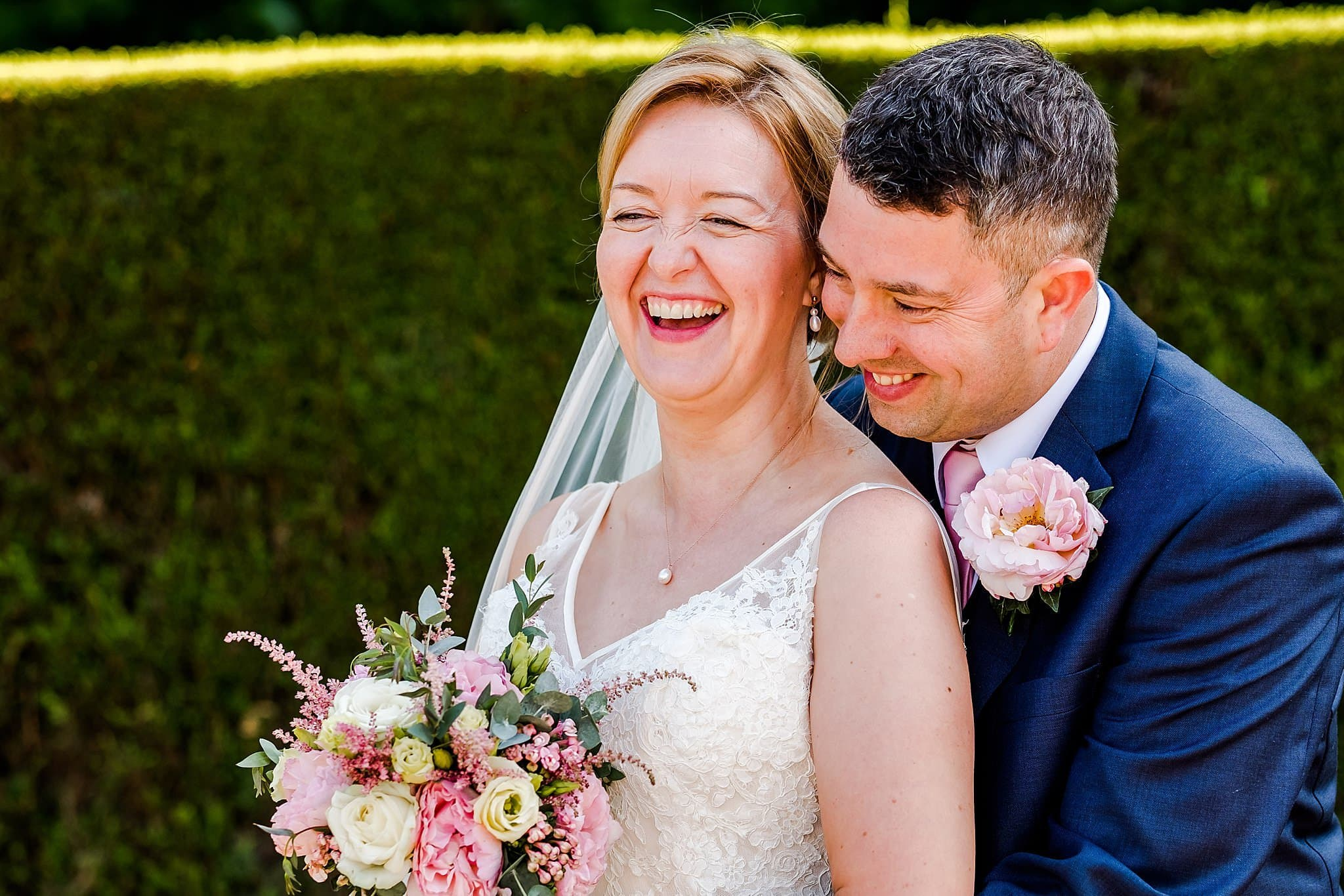 Bride and groom laugh at a joke at Newton House Barns