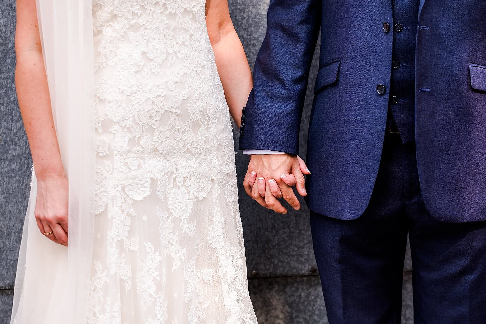 Close up of bride and grooms hand holding