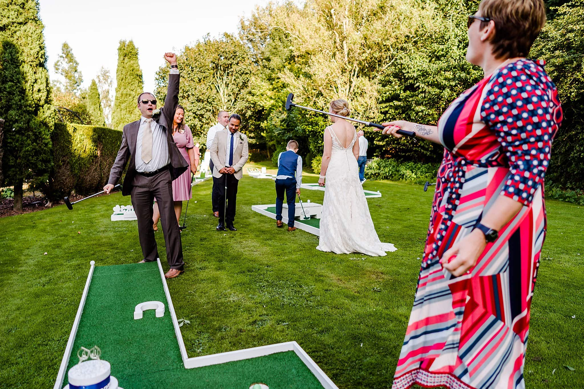 Wedding guest raises his arms after potting his golf ball at Newton House Barns