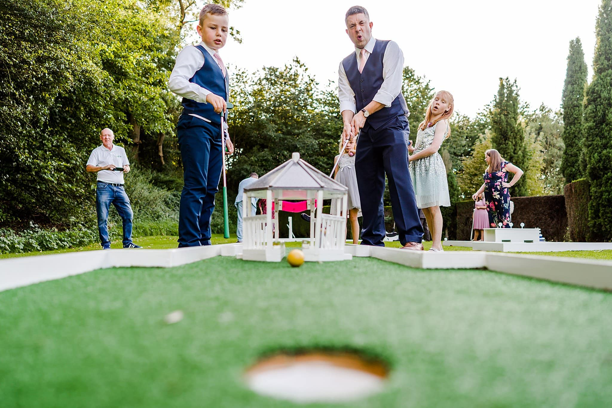 Low down view of groom and his son playing miniature golf at Newton House Barns