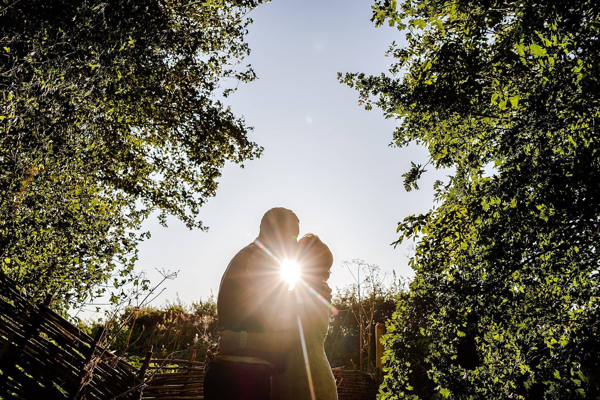 Bride and groom kiss whilst sun beams between them at Newton House Barns