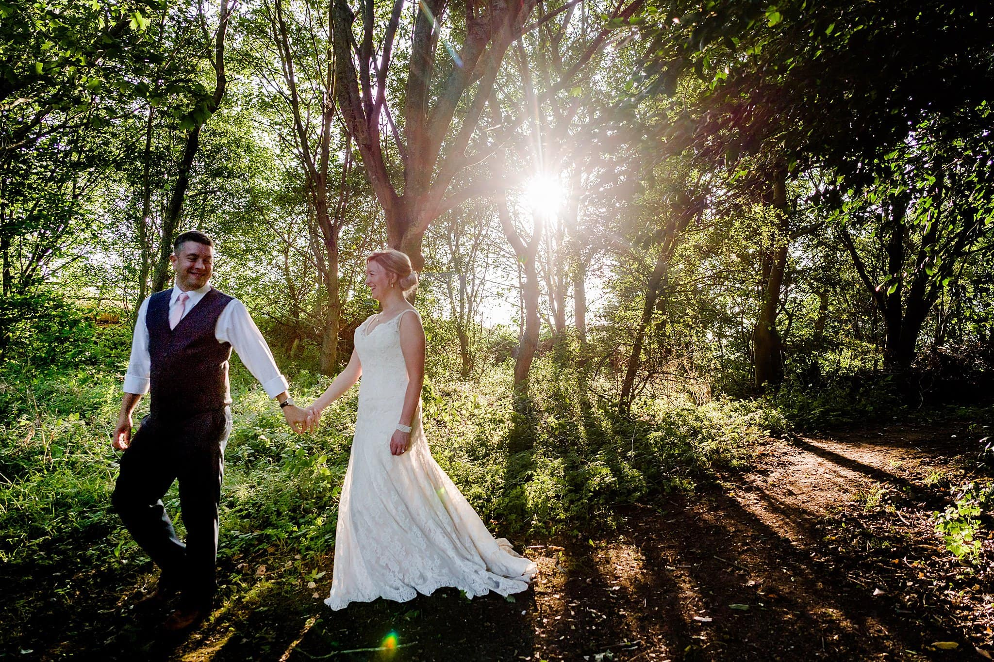 Bride and groom walk through woodland during sunset at Newton House Barns