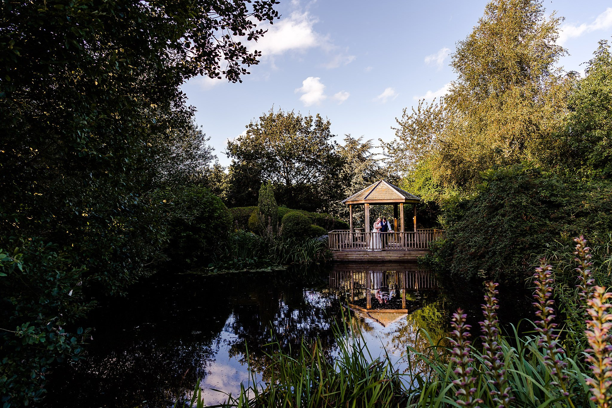 Wide shot showing the bride and groom in the gazebo over the water at Newton House Barns