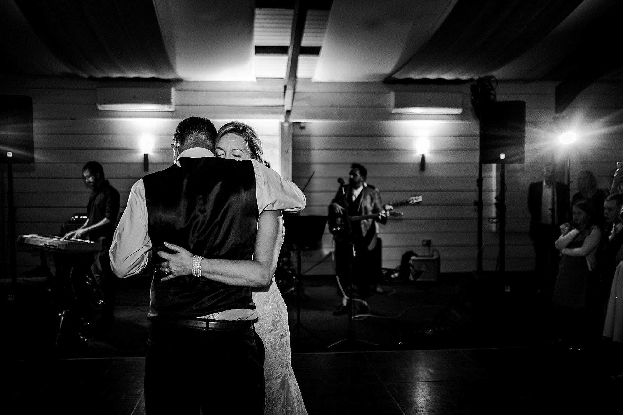 Bride and groom cuddle close during their first dance at Newton House Barns