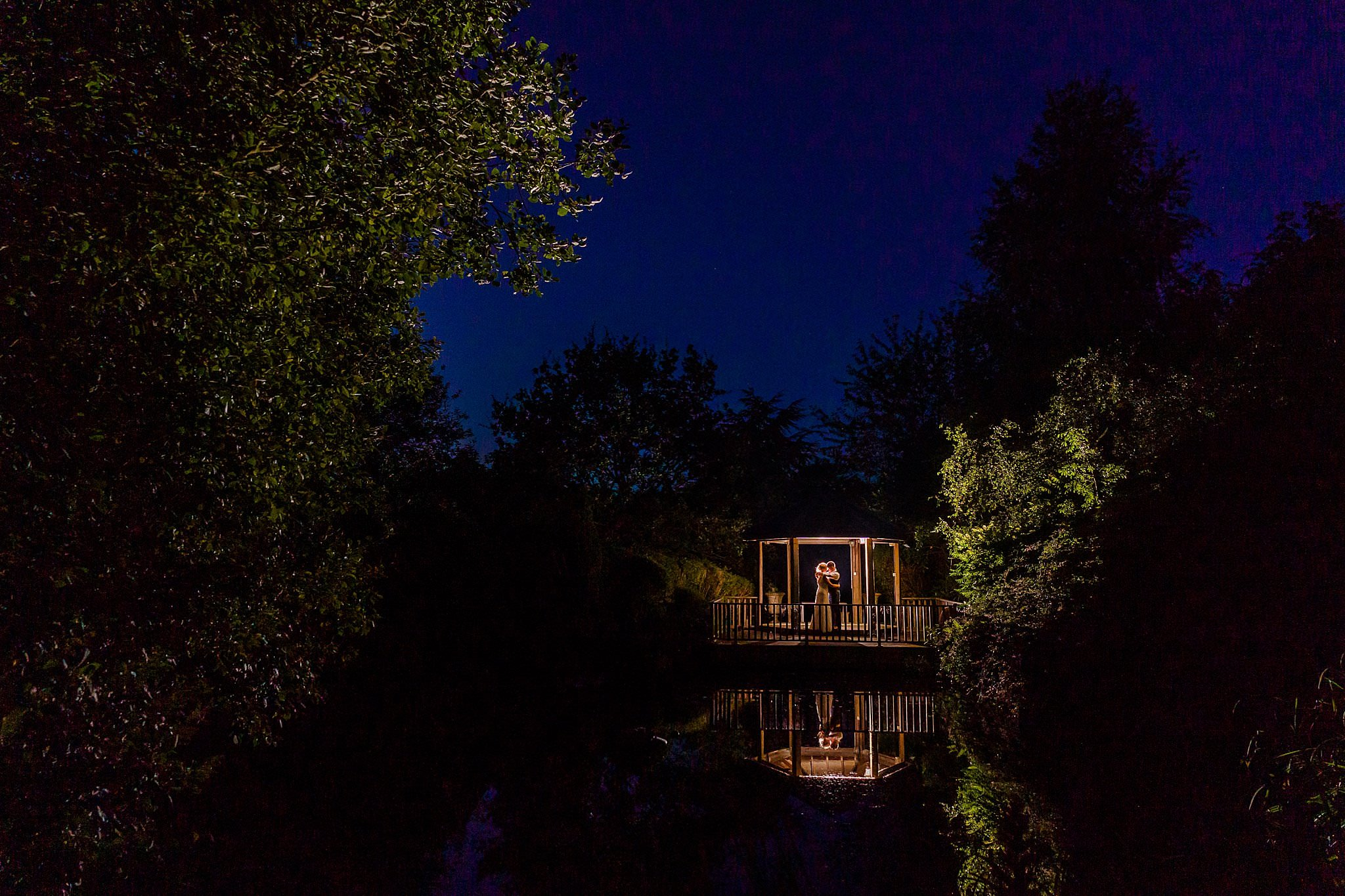 Night time flash photo of bride and groom kissing in gazebo over water at Newton House Barns