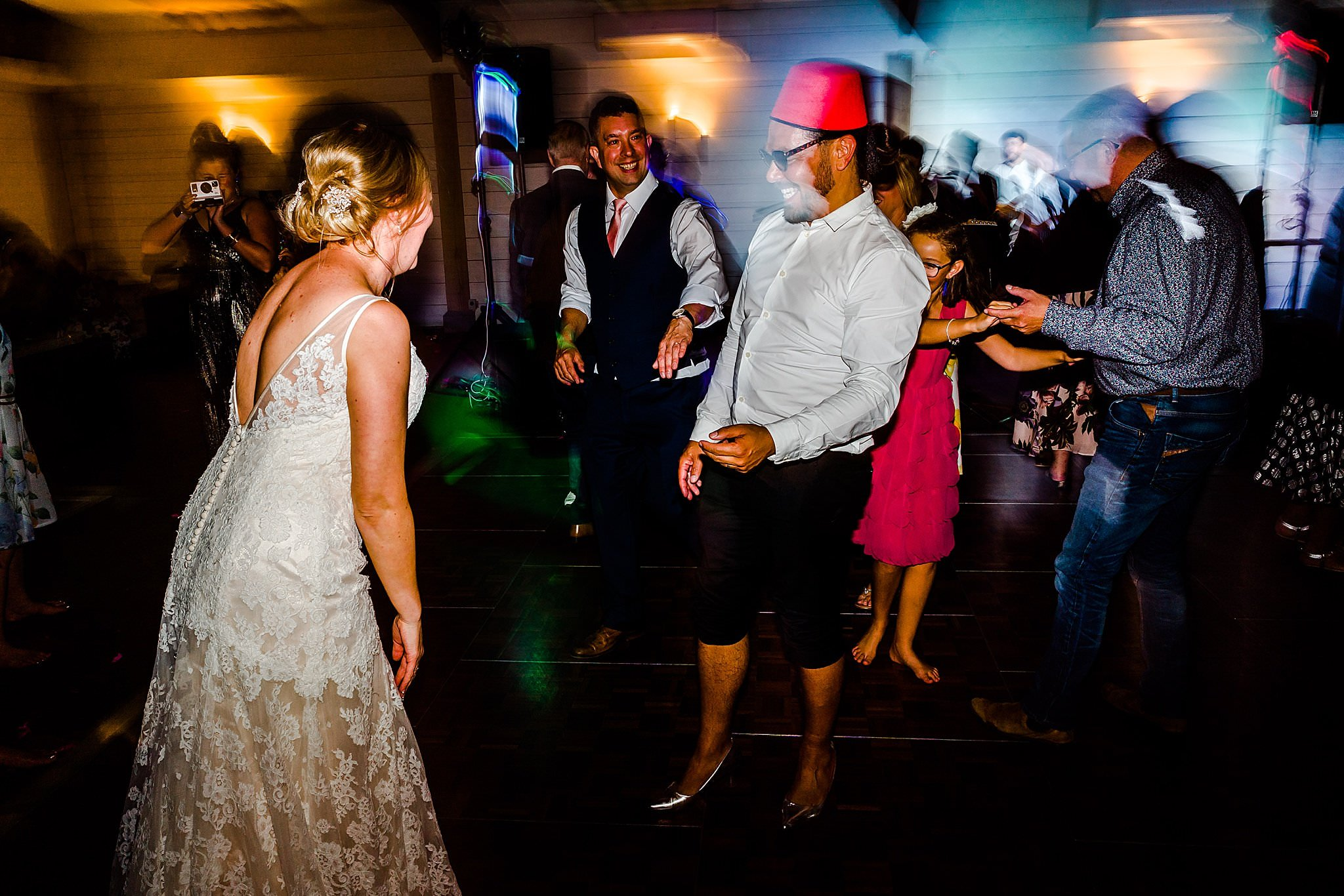 Wedding guests wearing his wife's shoes on dancefloor at Newton House Barns
