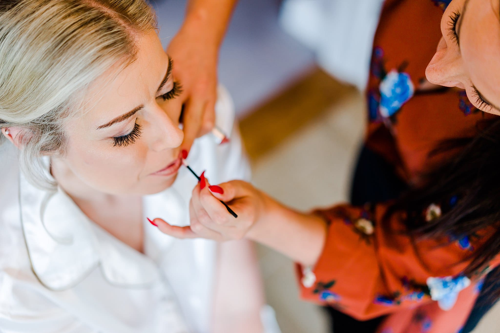 Bride gets her lips touched up before her wedding at Carriage Hall