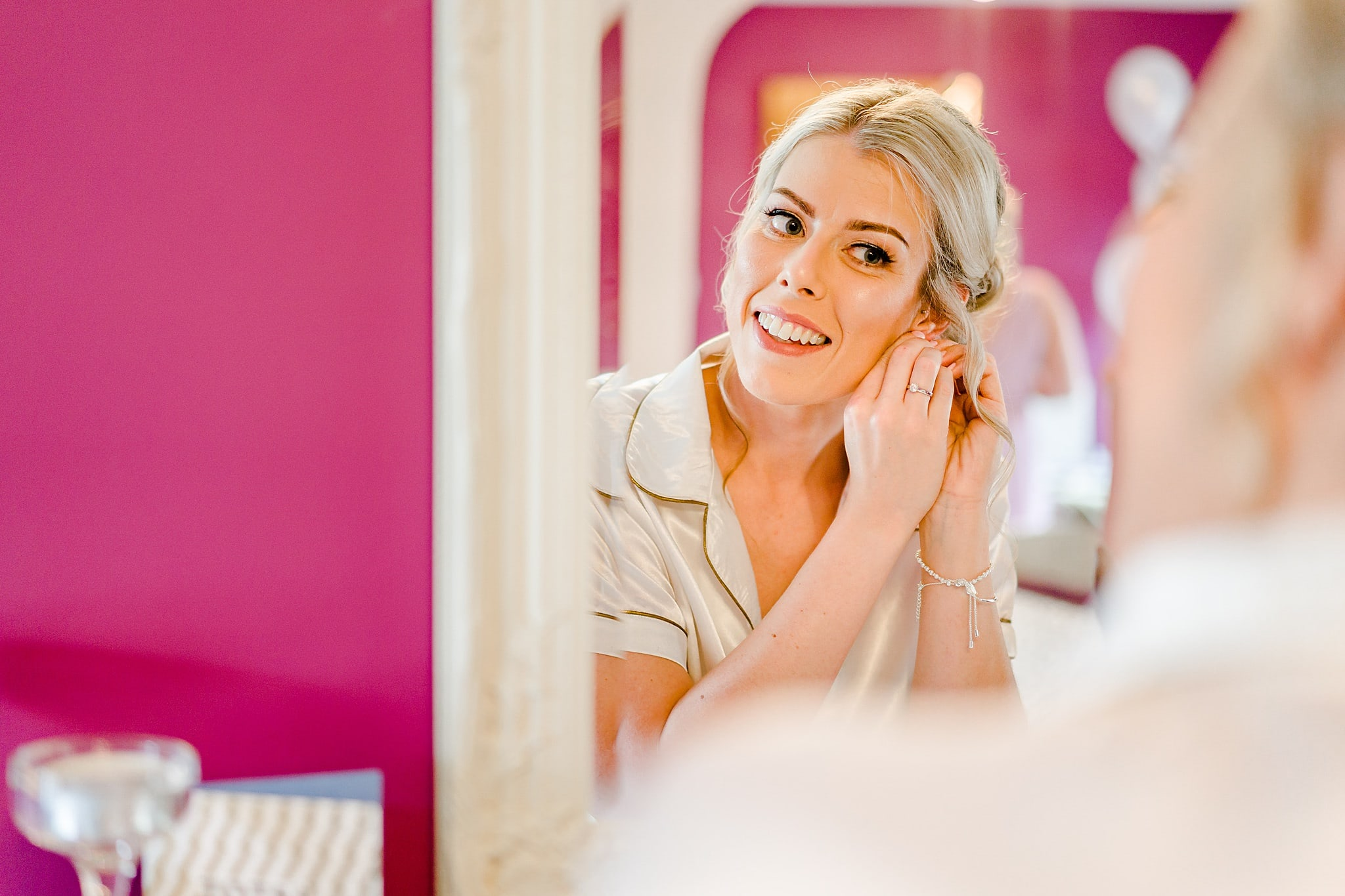 Bride smiles in mirror whilst adjusting ear rings