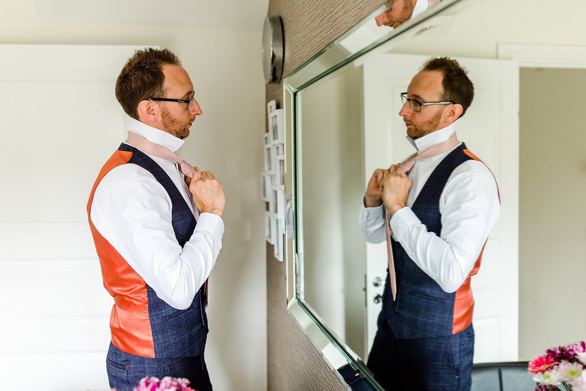 Groom adjusts his tie in mirror before his wedding at Carriage Hall