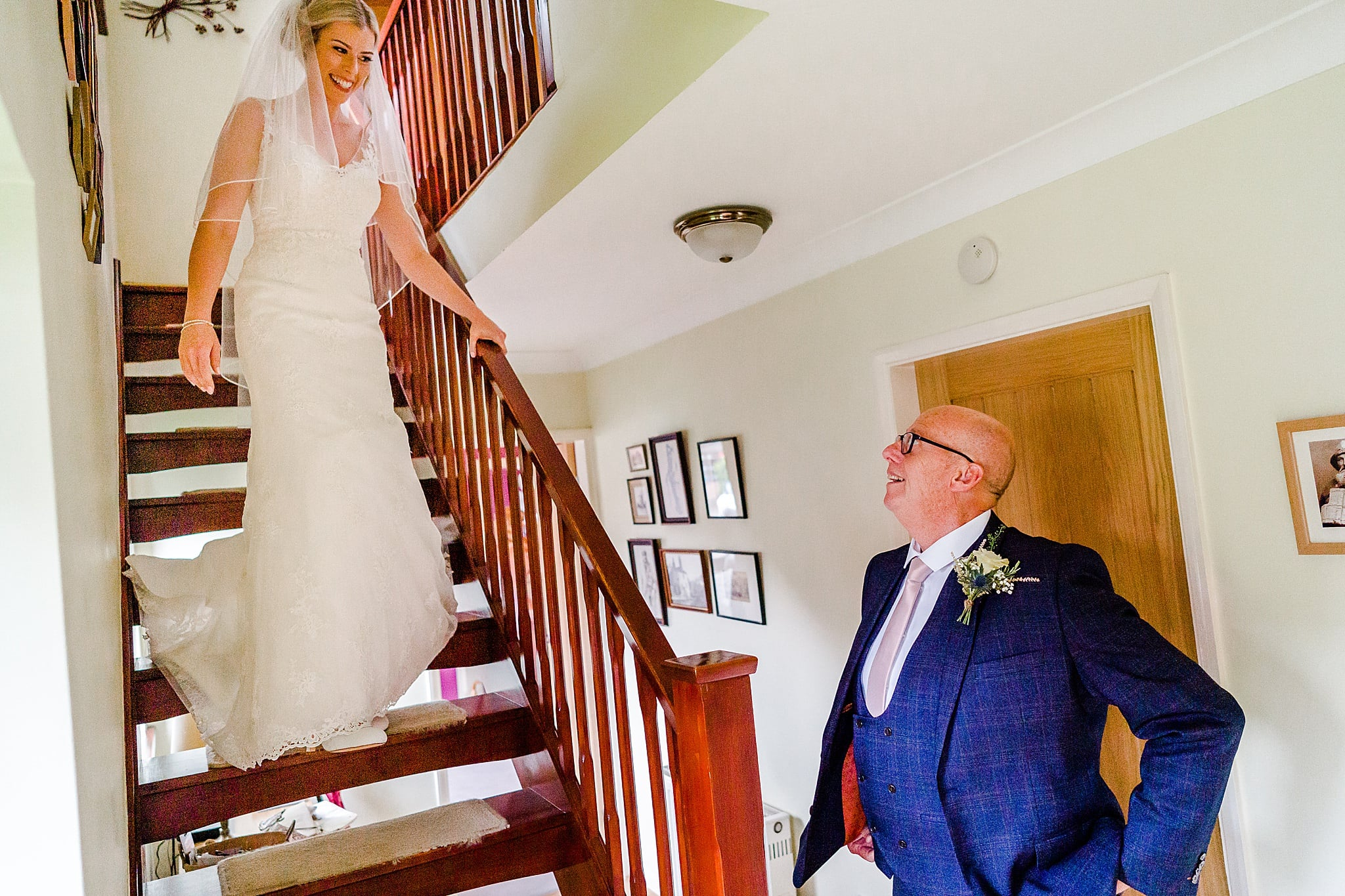 Bride's father watches as his daughter walks down the stairs in her wedding dress