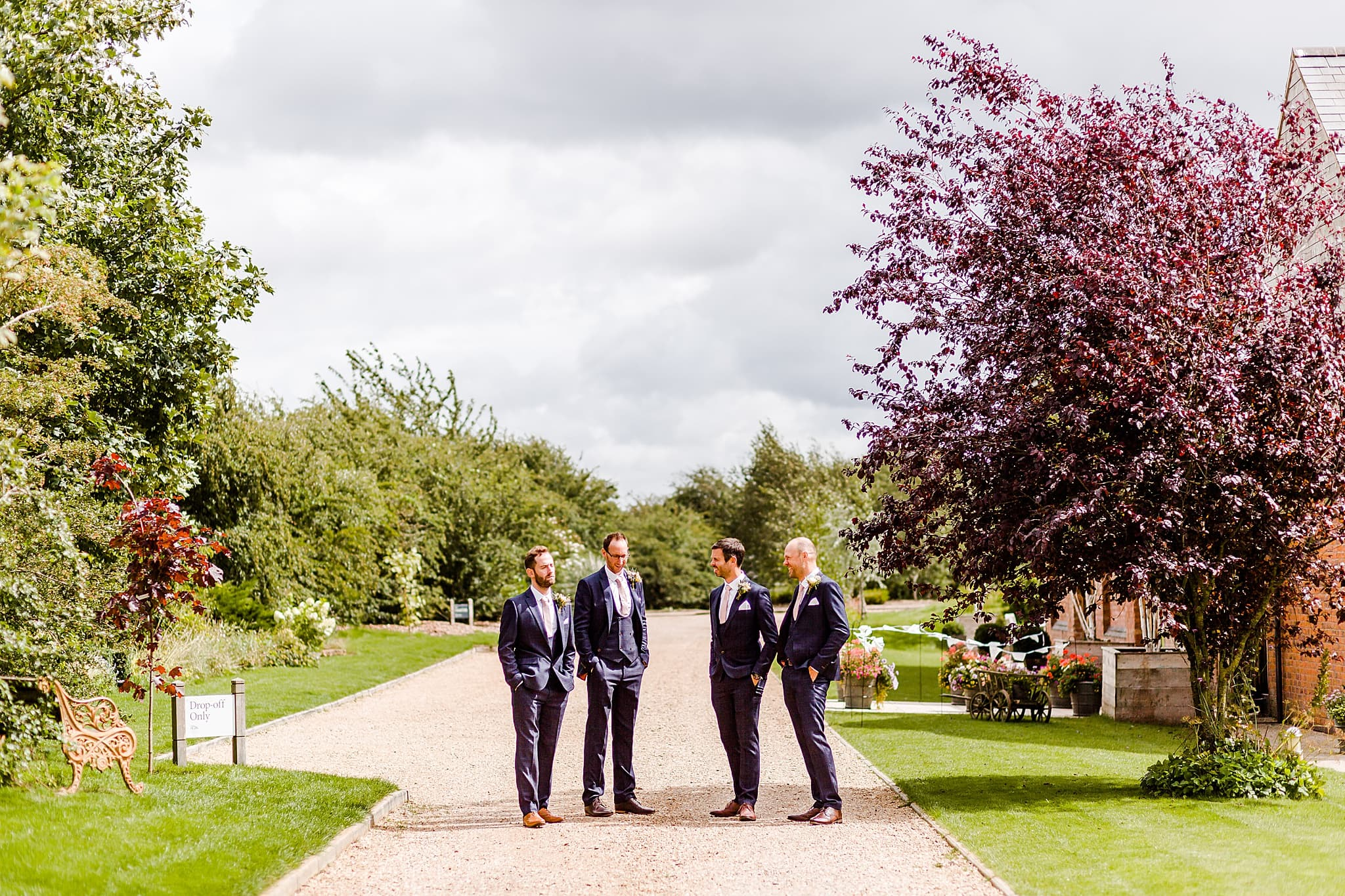 Groom and groomsmen pose outside of carriage hall