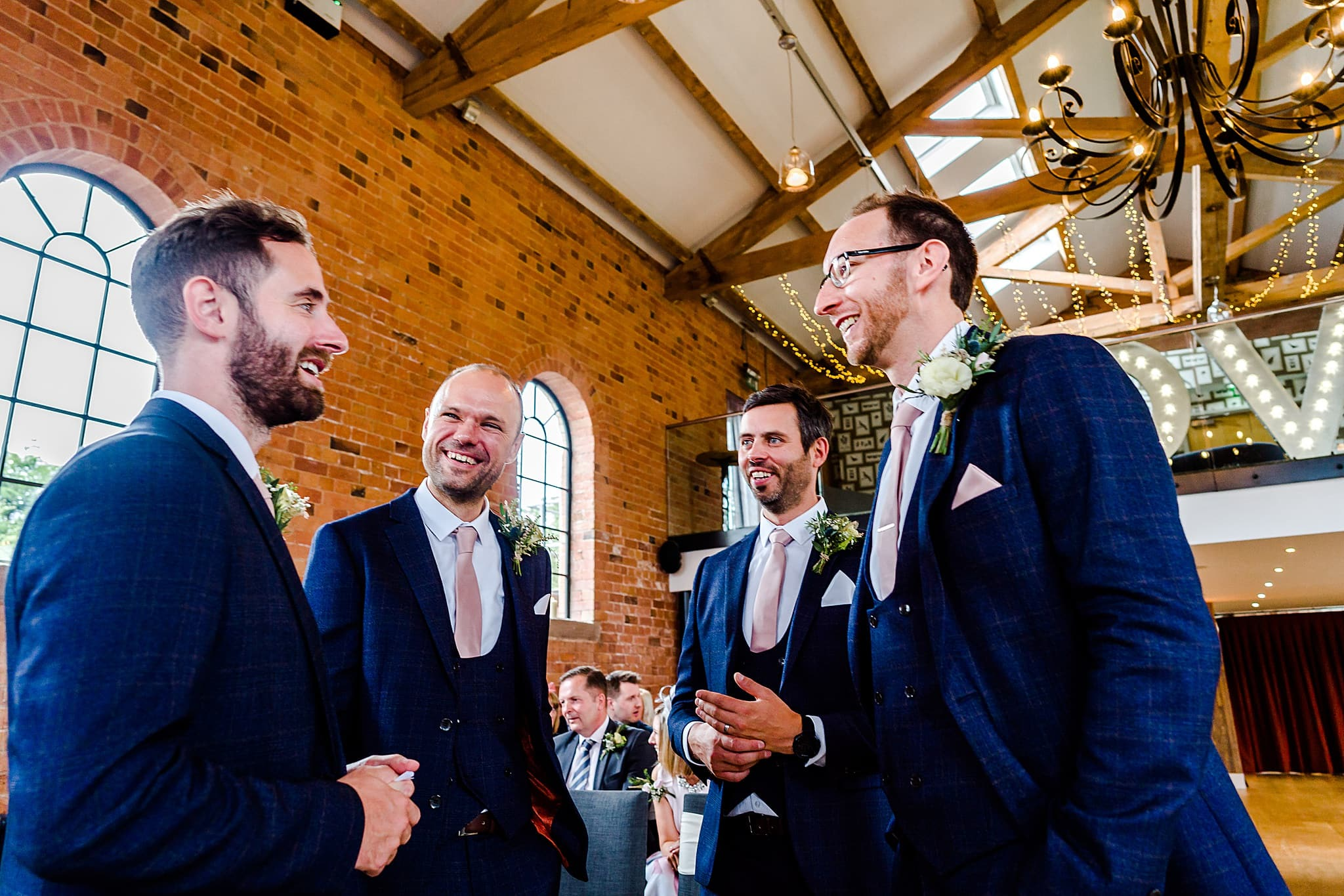 Groomsmen laugh waiting for bride to arrive