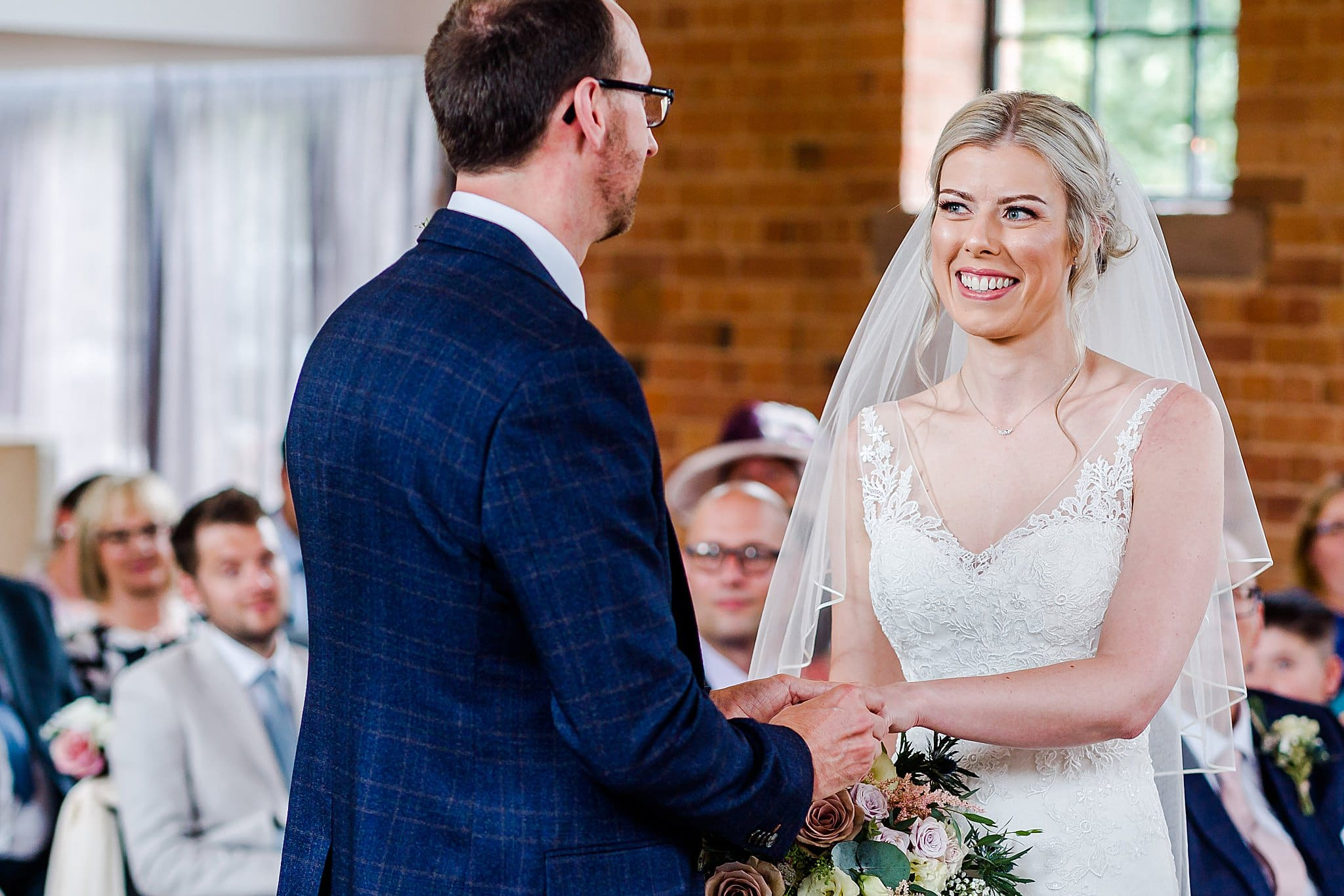 Bride smiles at groom whilst holding hands at Carriage Hall