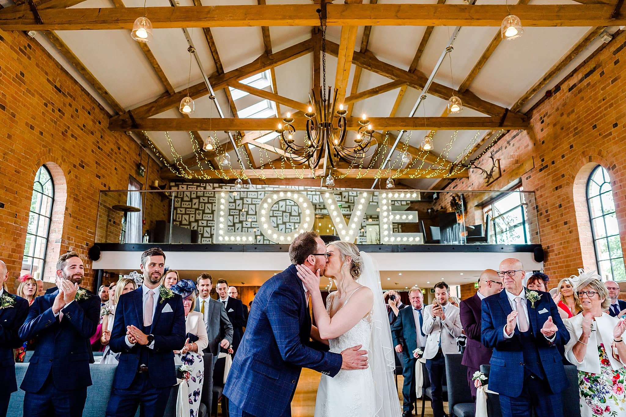 Bride and groom kiss with LOVE over their head at Carriage Hall