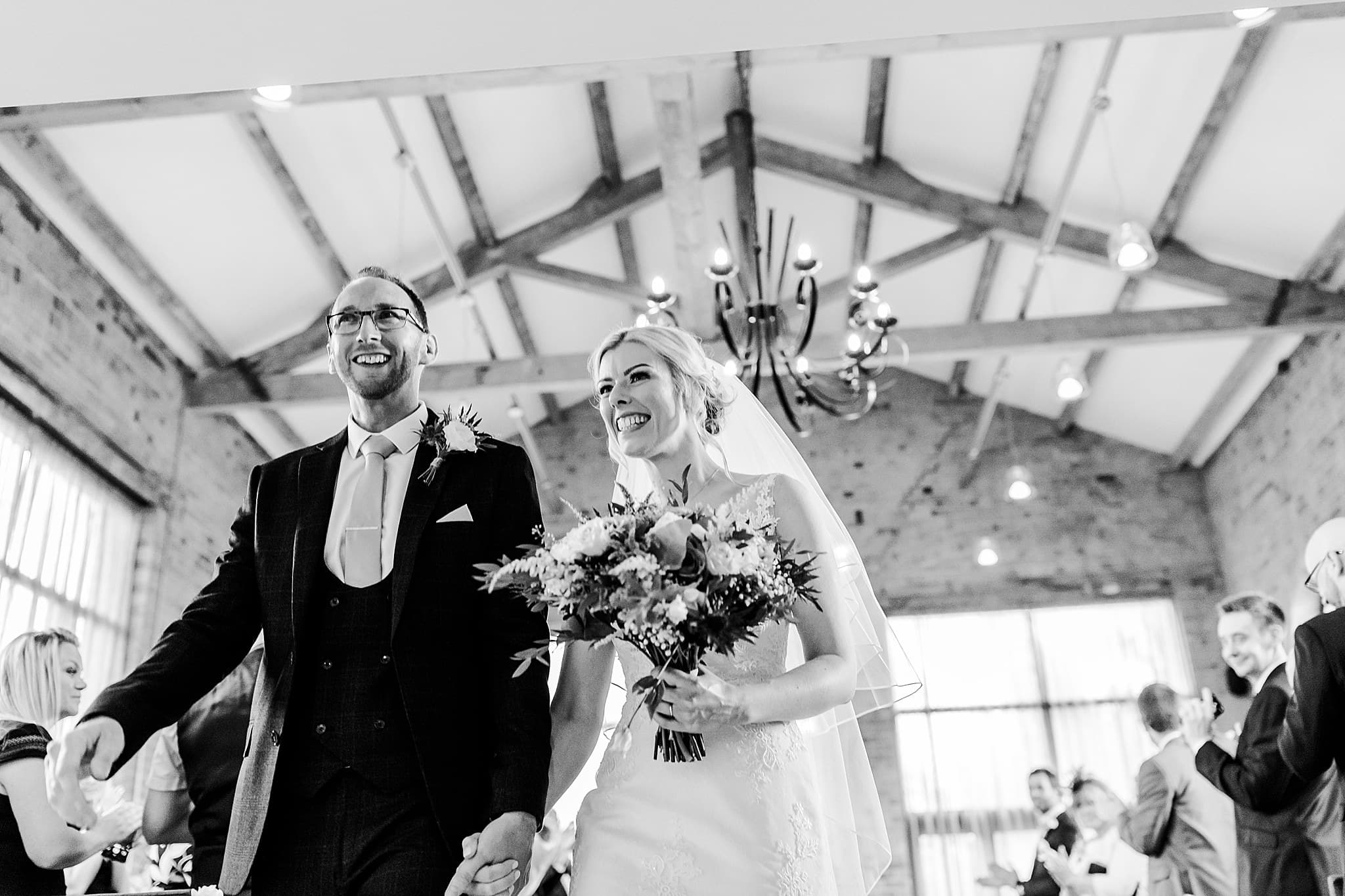 Bride and groom smile whilst walking back down the aisle