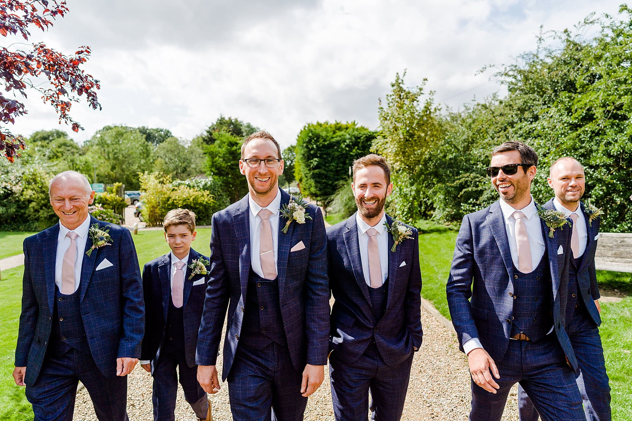Groom and his groomsmen walk down the path at Carriage Hall