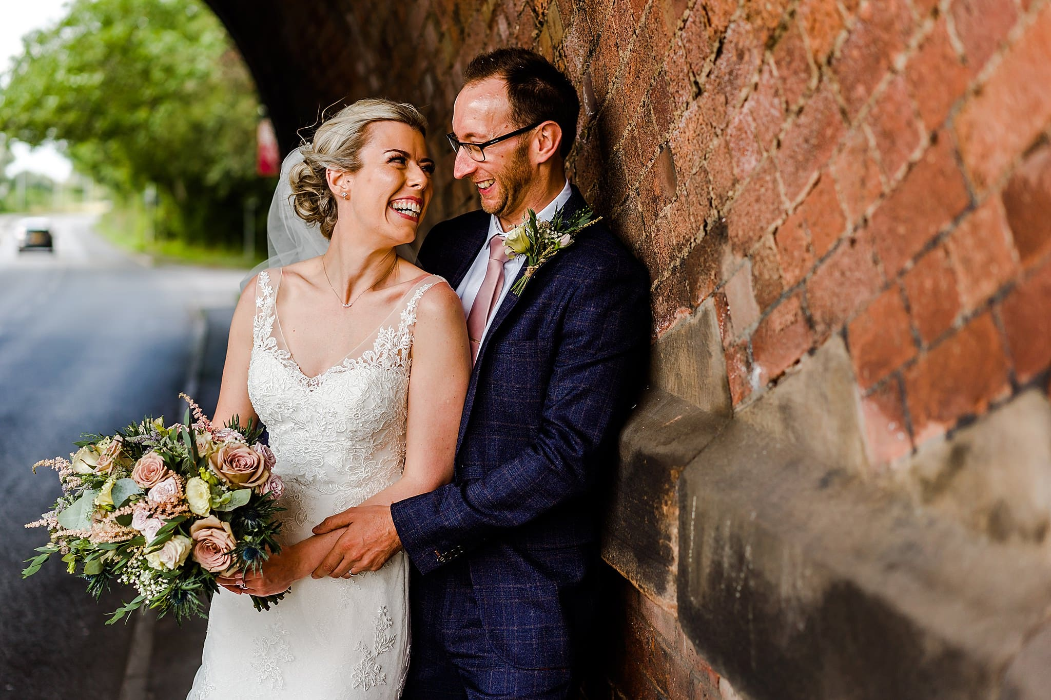 Bride and groom smile and cuddle close under the bridge at Carriage Hall