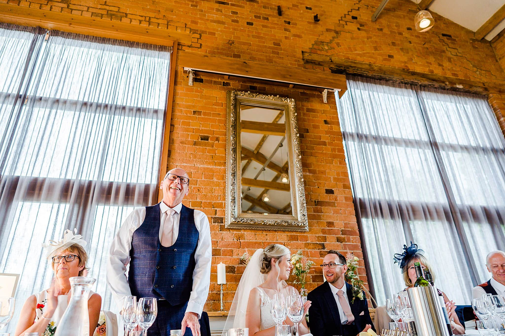 Bride's father stands to start his wedding speech