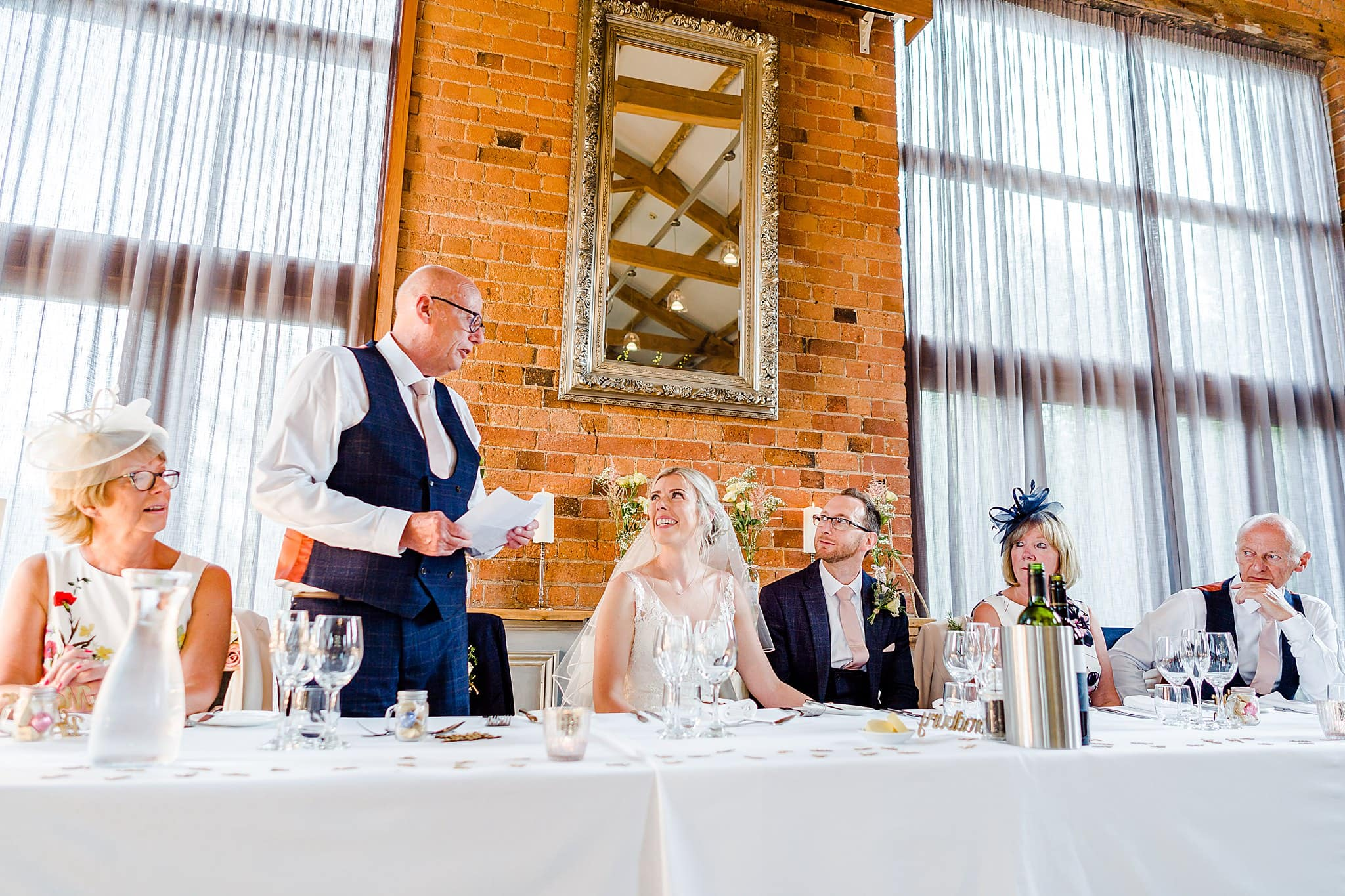 Bride's father looks at bride during his wedding speech at Carriage Hall