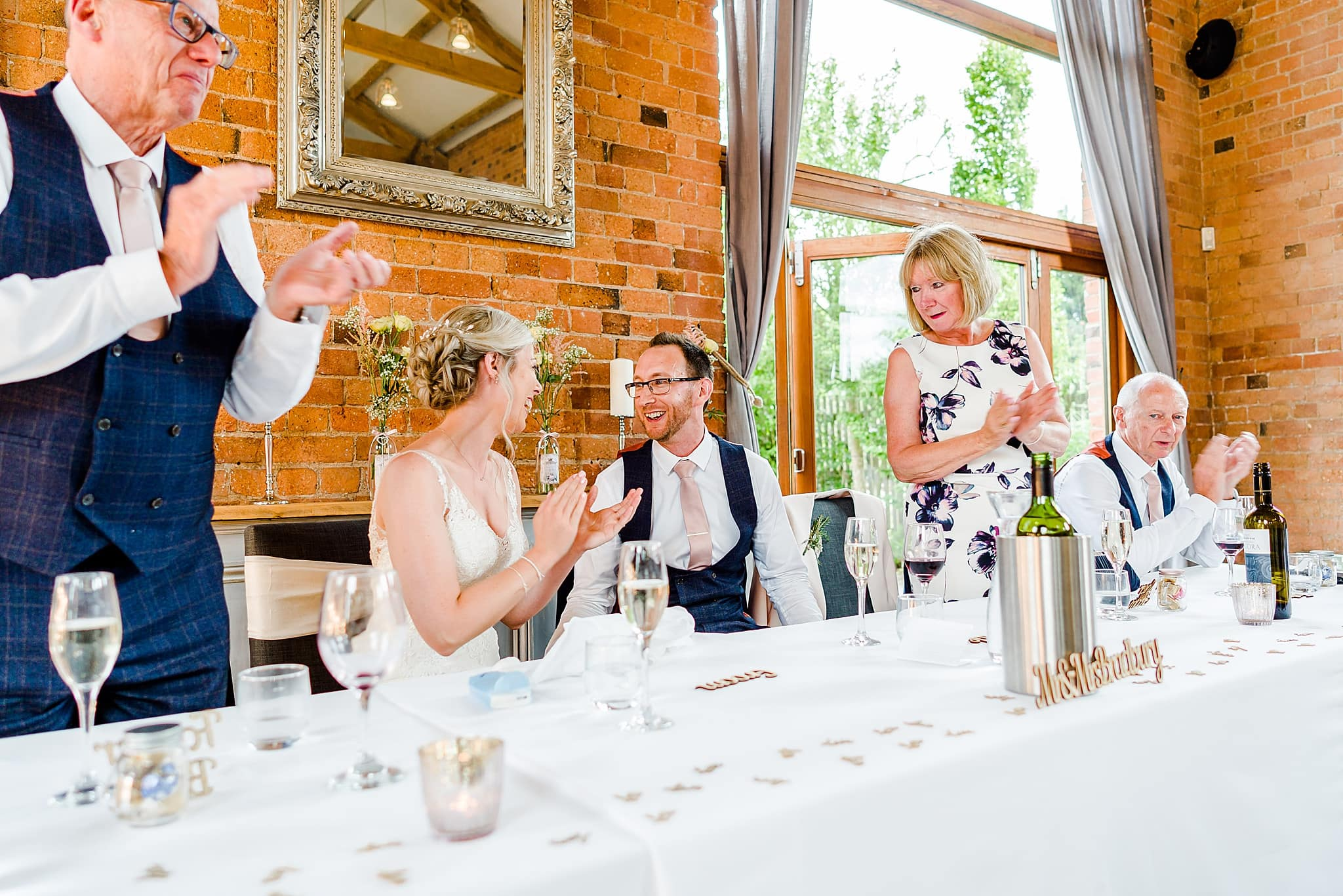 Everyone applauds the groom after he finishes his wedding speech at Carriage Hall