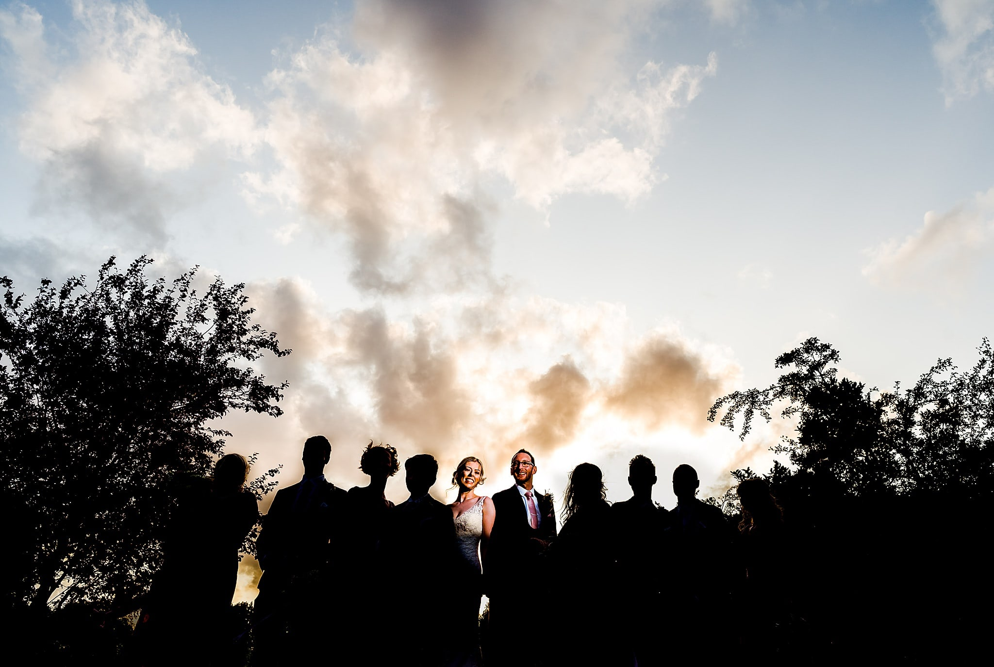 Silhouette shot of wedding party with bride and groom lit up by flash in front of moody sky