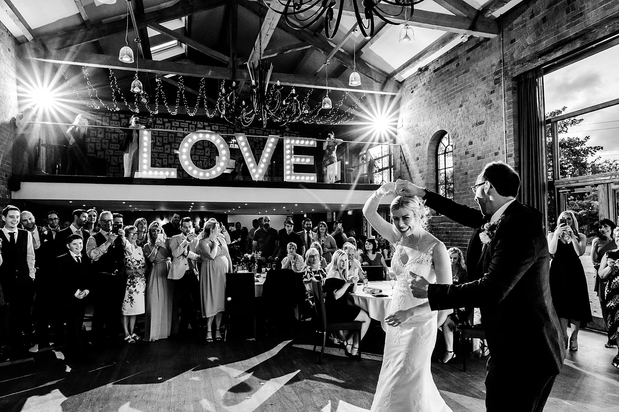 Bride and groom perform their first dance at Carriage Hall with their guests all watching