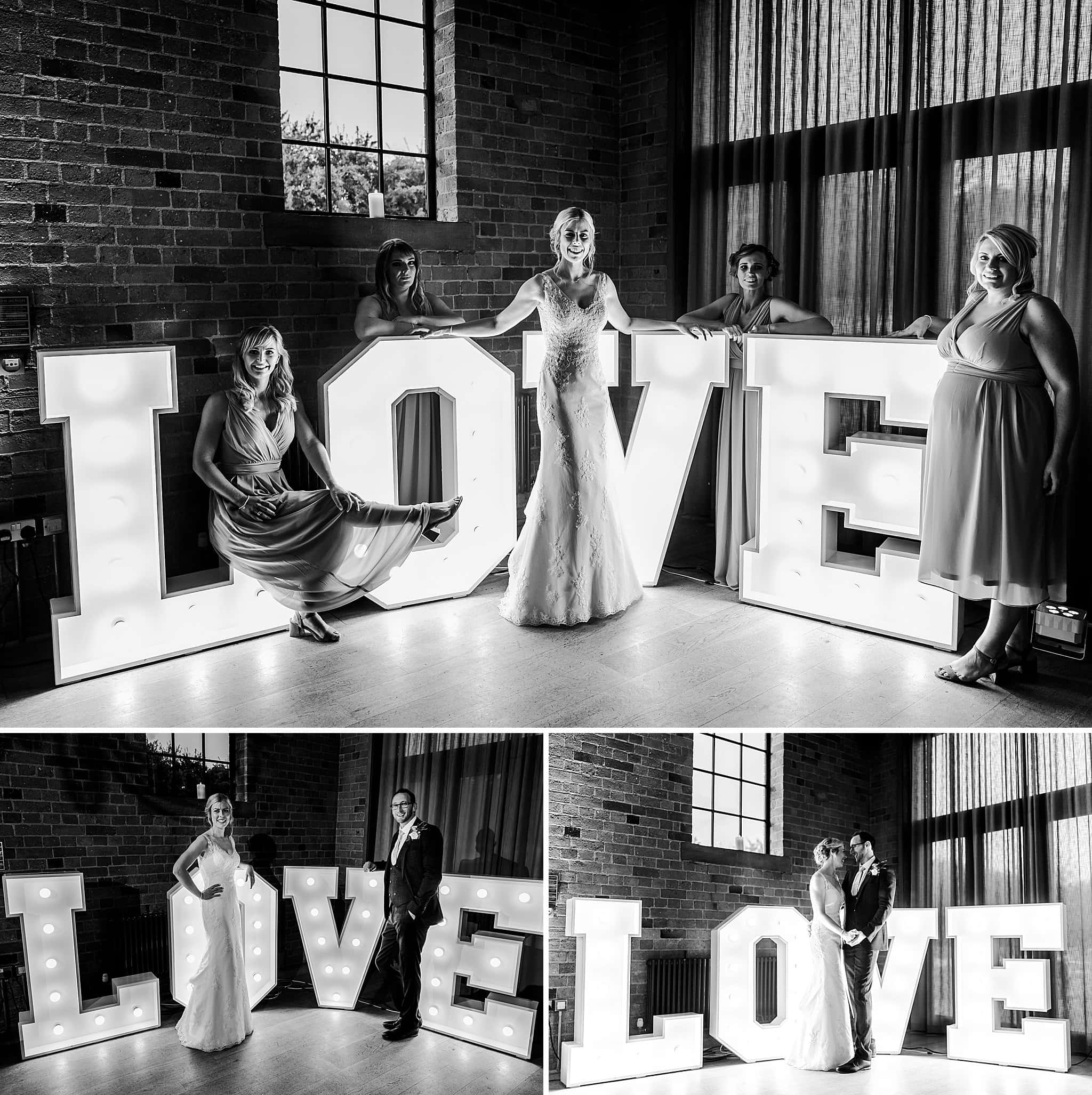 Bride, groom and bridesmaids all pose in front of Love letters at Carriage Hall