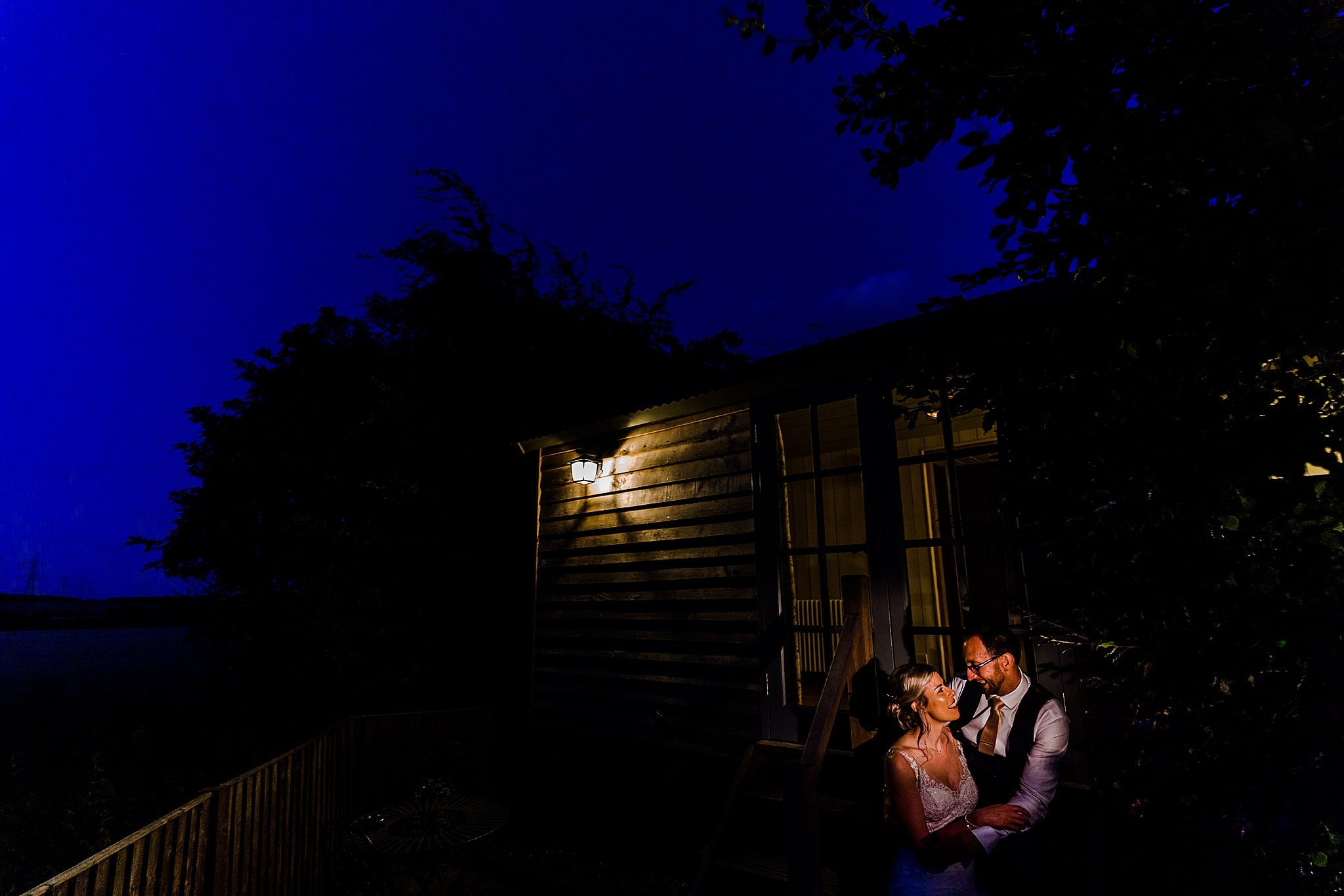 Bride and groom sit on the steps of the bridal carriage at night at Carriage Hall