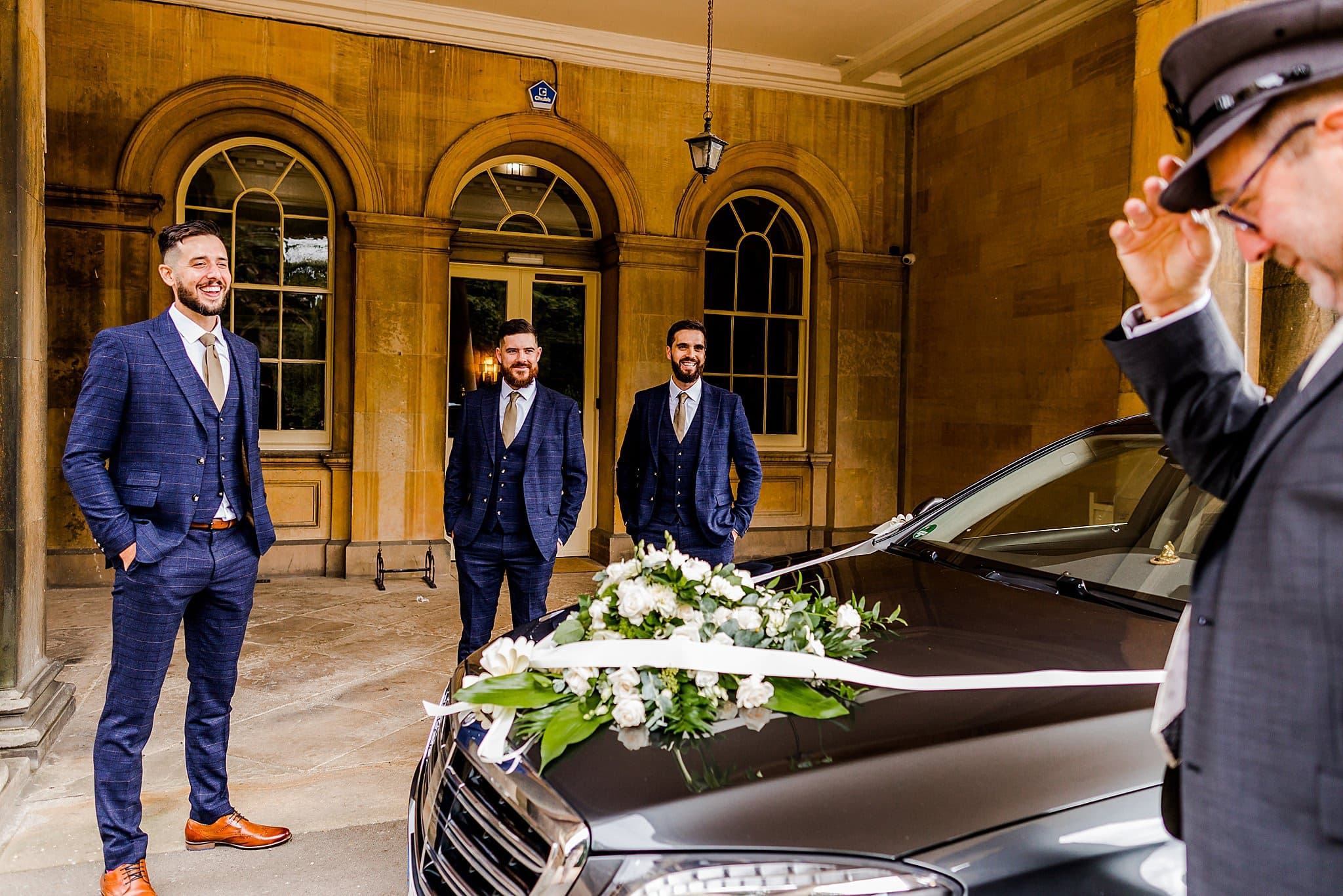 Groom and his groomsmen share a laugh with their car driver outside Prestwold Hall