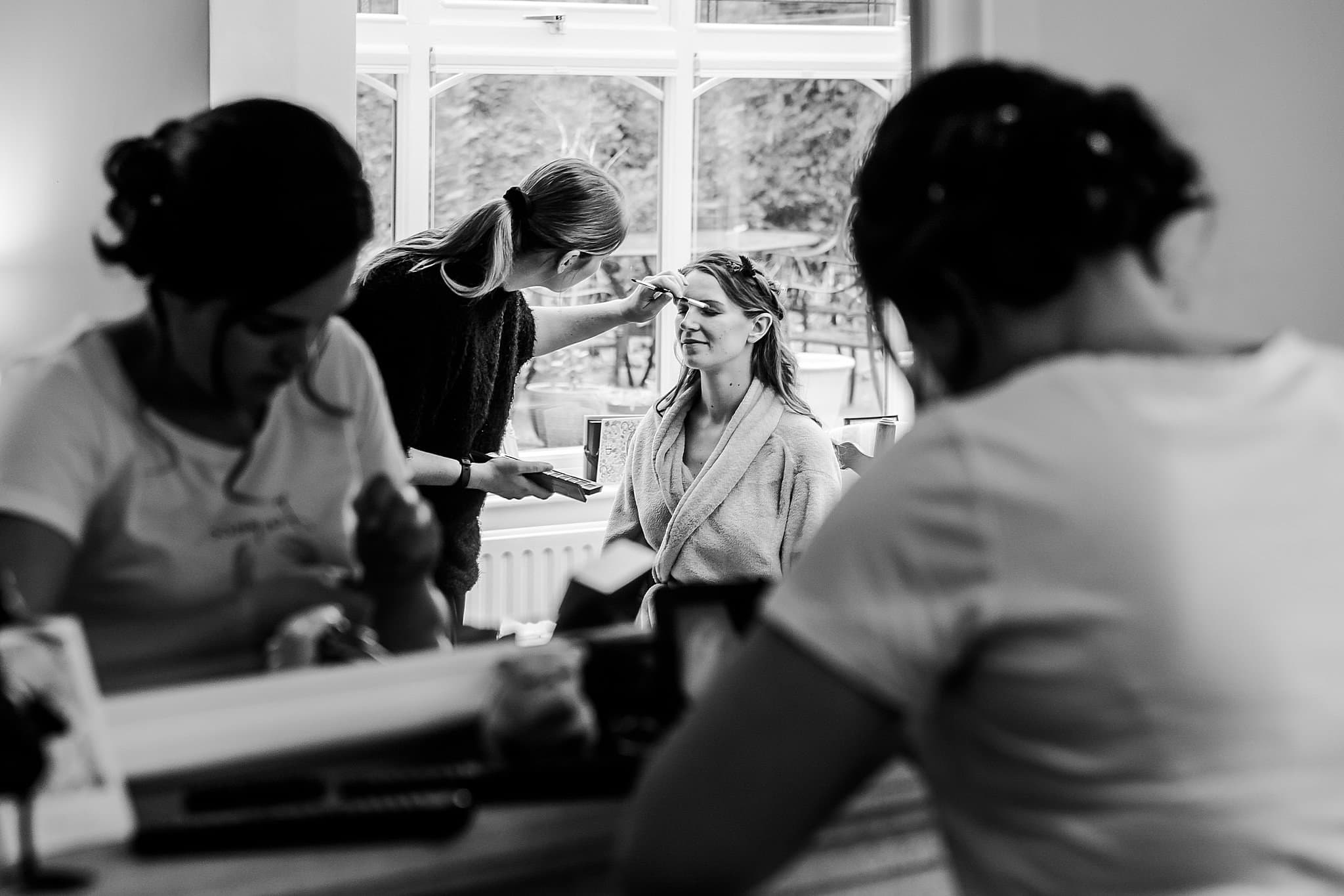 Bride has her make up done whilst her bridesmaid does her own makeup in the mirror