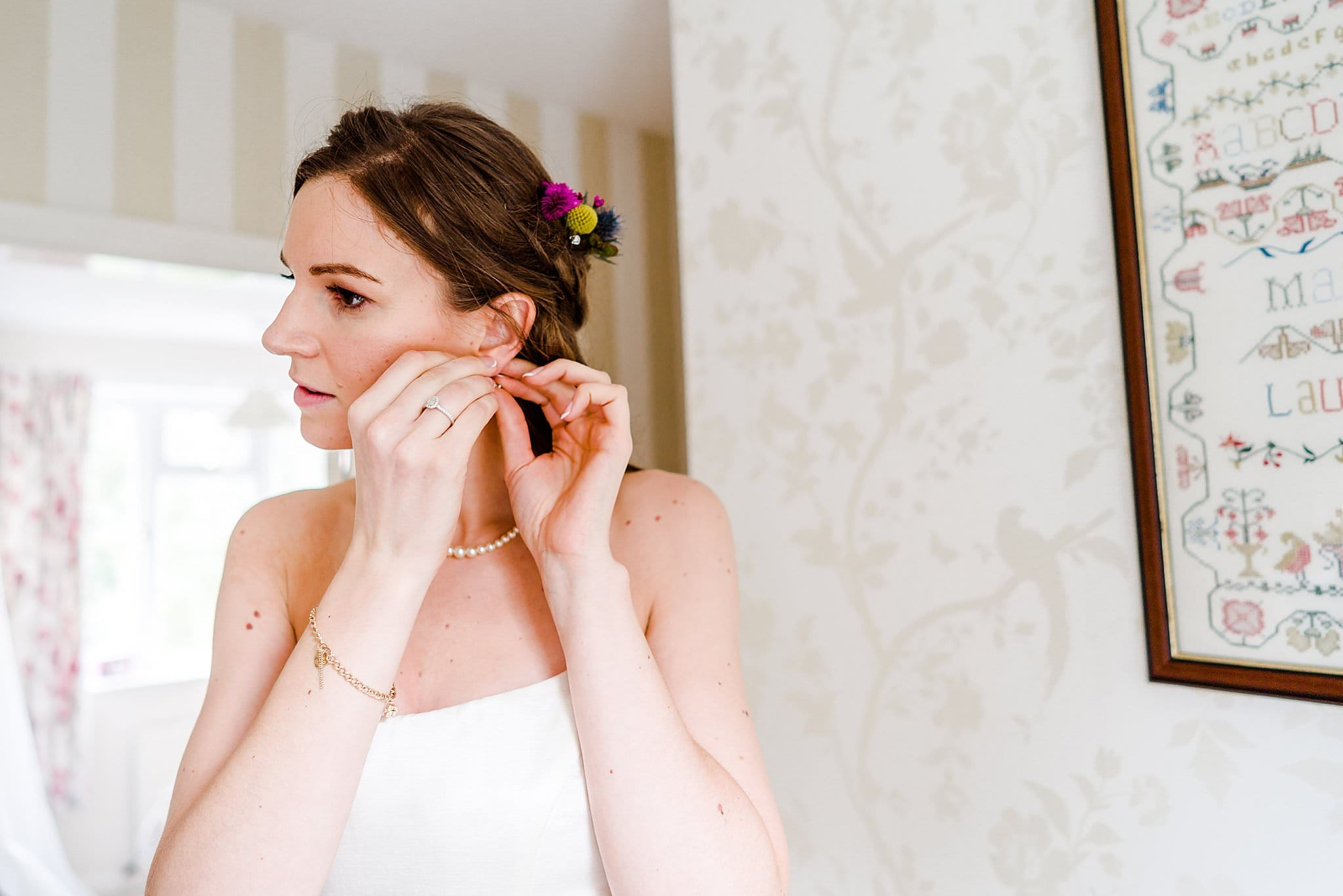 Bride adjusts her ear rings whilst getting ready for her wedding