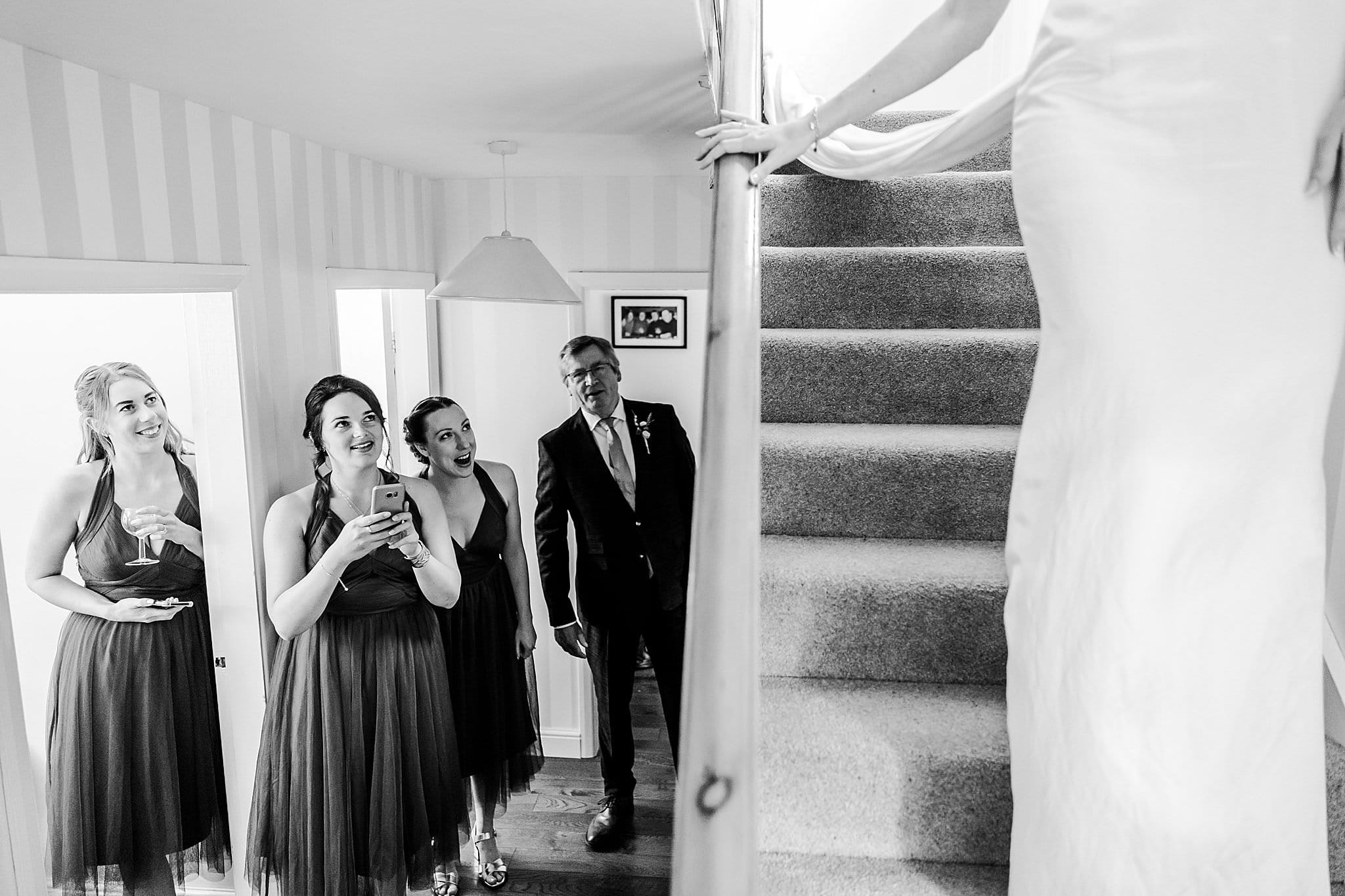 Bridesmaids and bride's father wait downstairs as bride comes down in her wedding dress