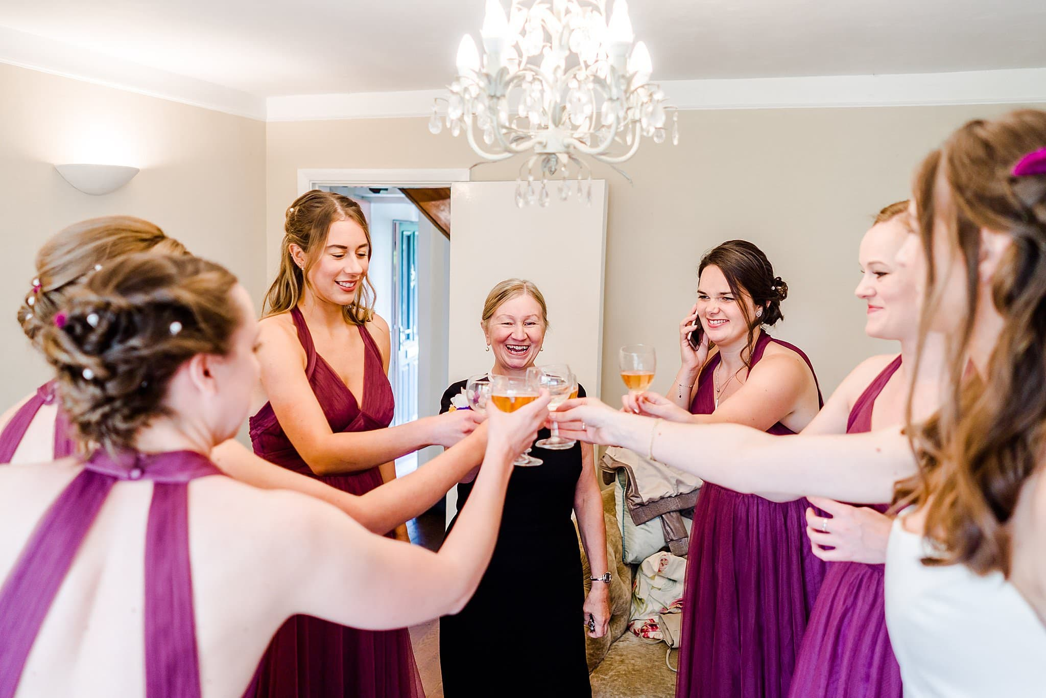 Bride, bridesmaids and bride's mother all clink glasses to toast the bride on her wedding day