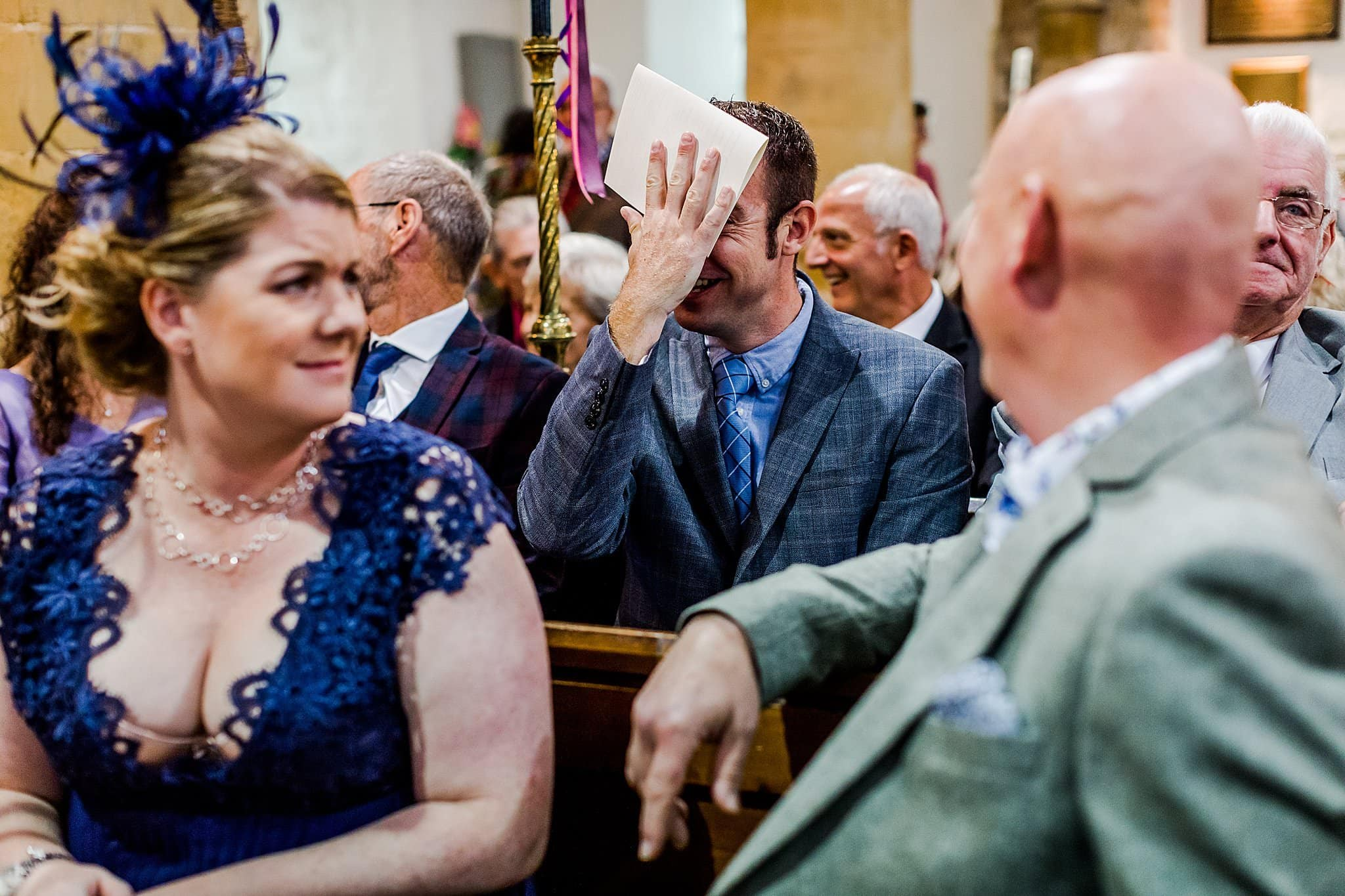 Wedding guest hits his head with a order of service whilst other guests look confused