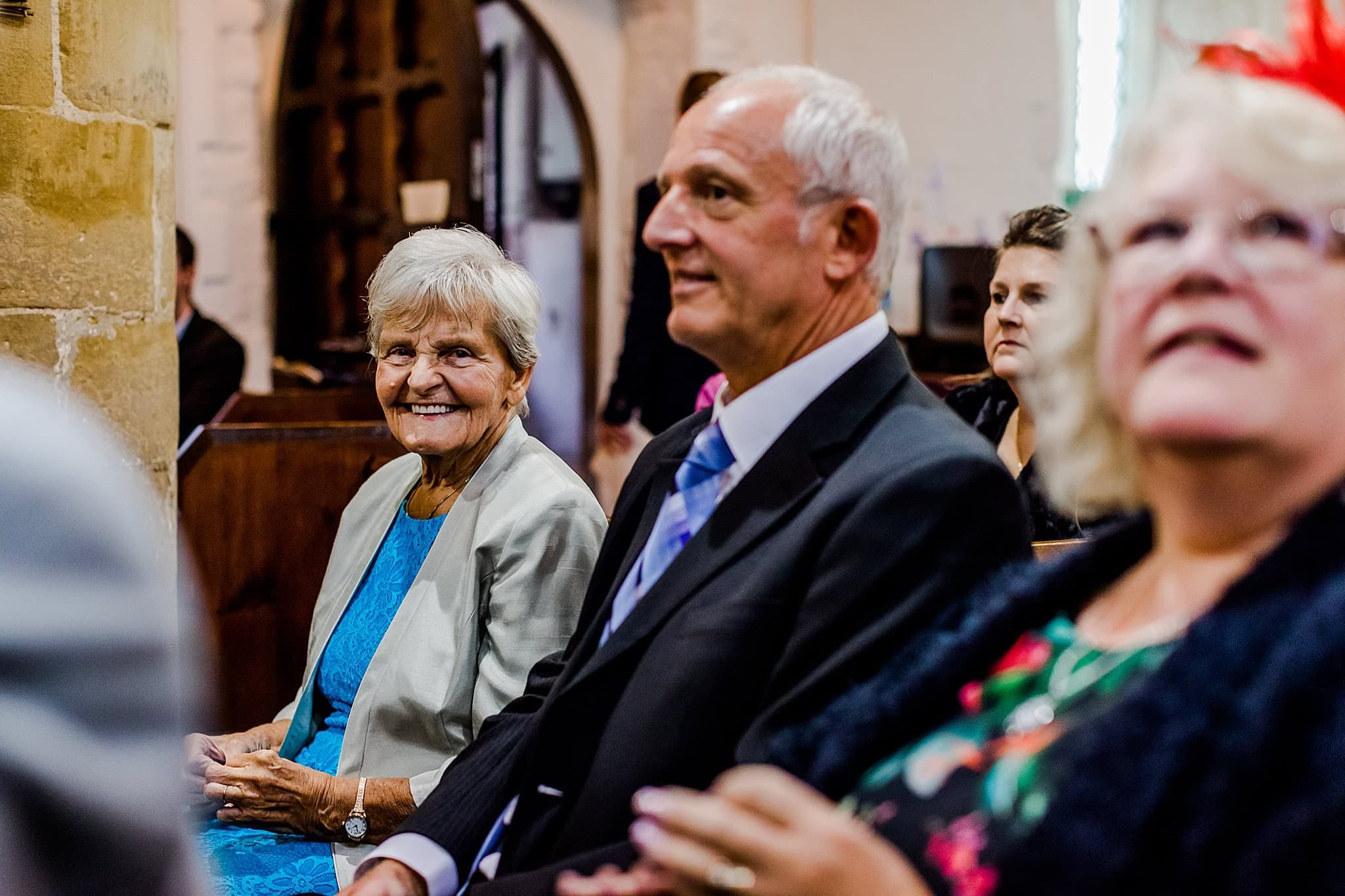 Grandmother smiles whilst waiting for the bride to arrive