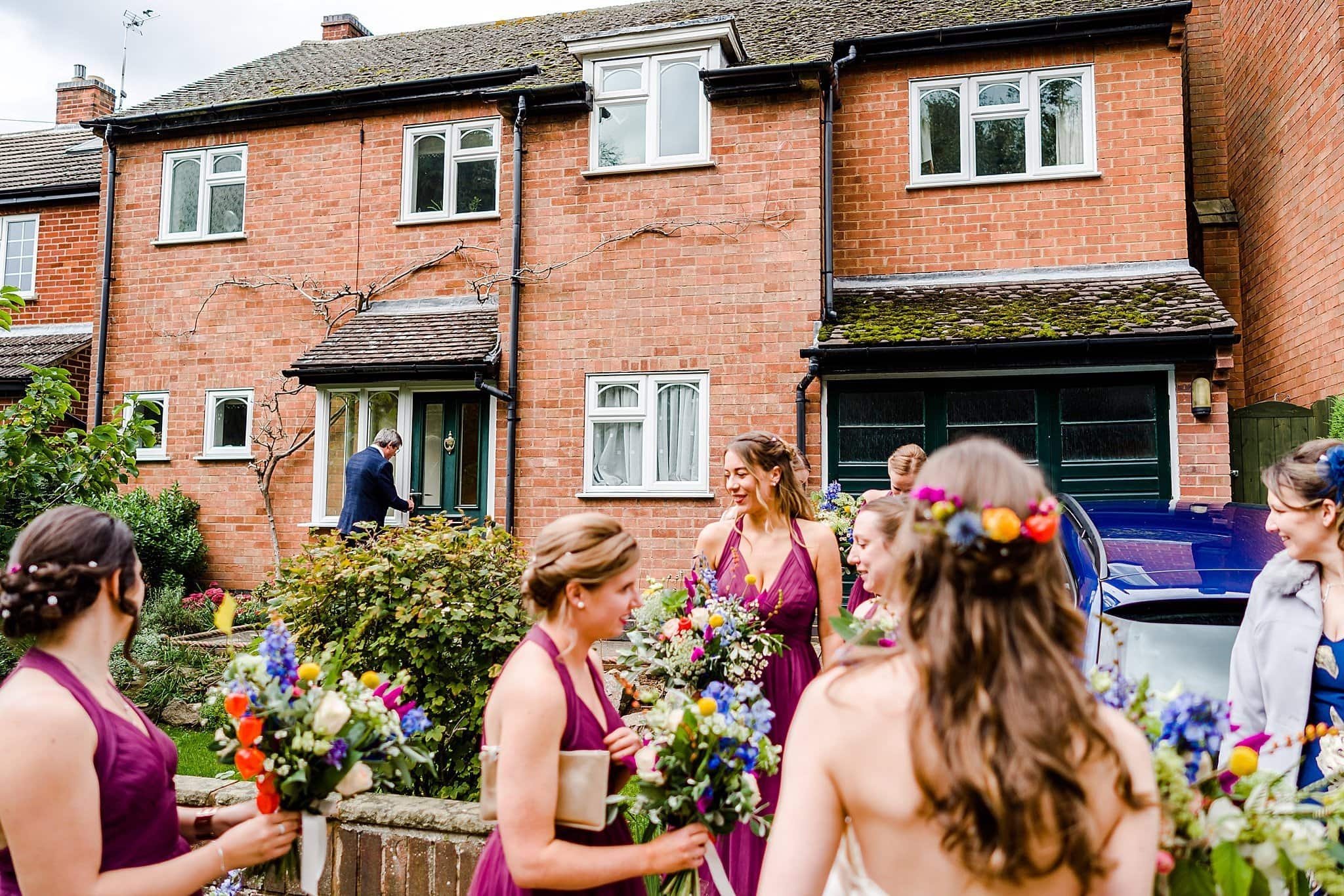 Bride's father locks the door whilst the bride and bridesmaid wait to walk to church