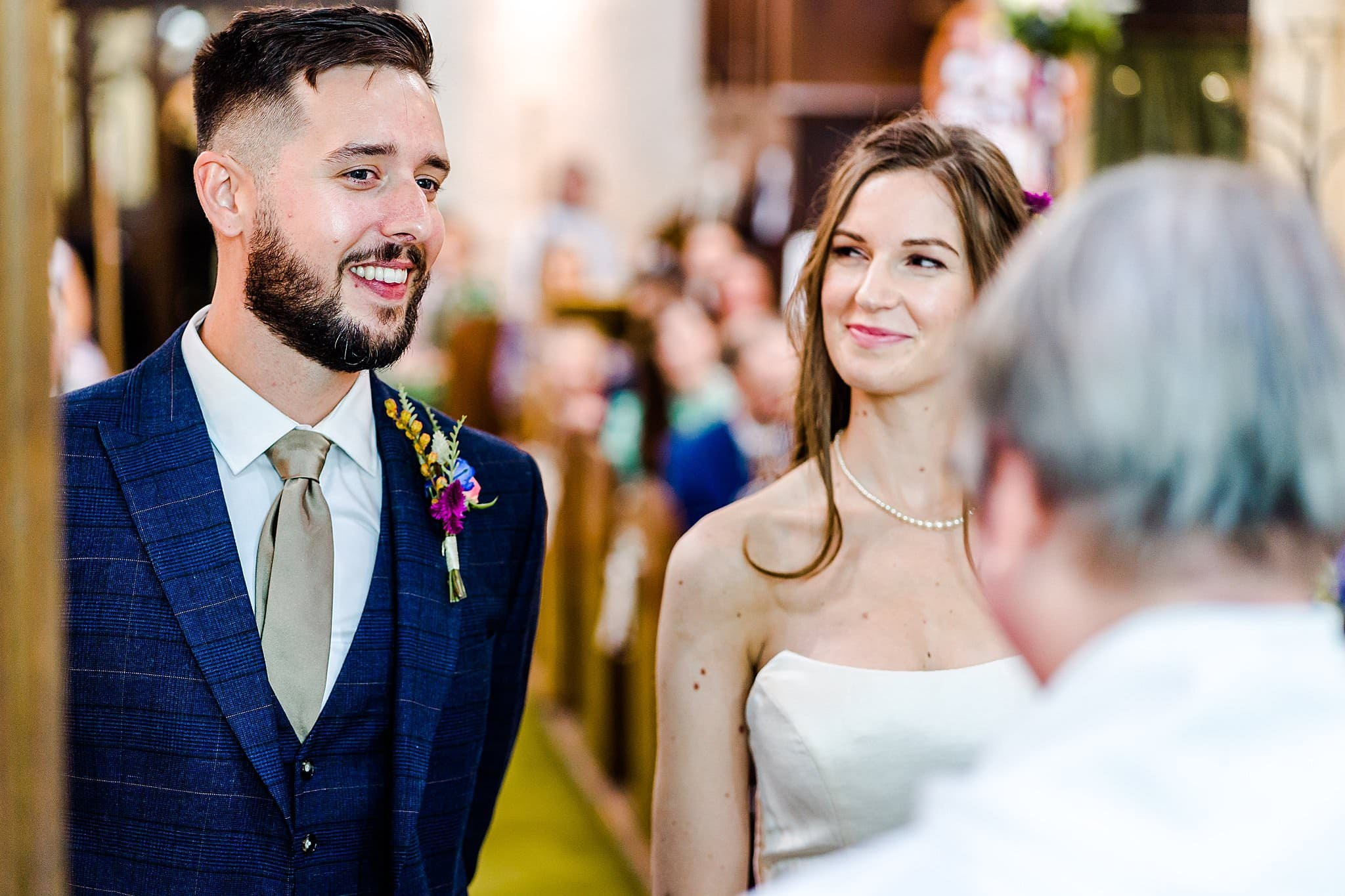 Bride looks at her groom whilst he smiles during their vows