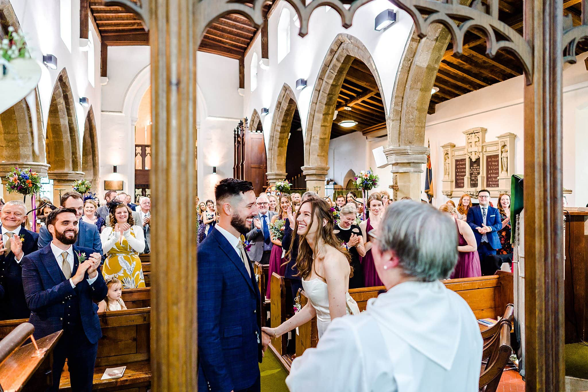 Wedding guests cheer and clap as bride and groom are told they are now married