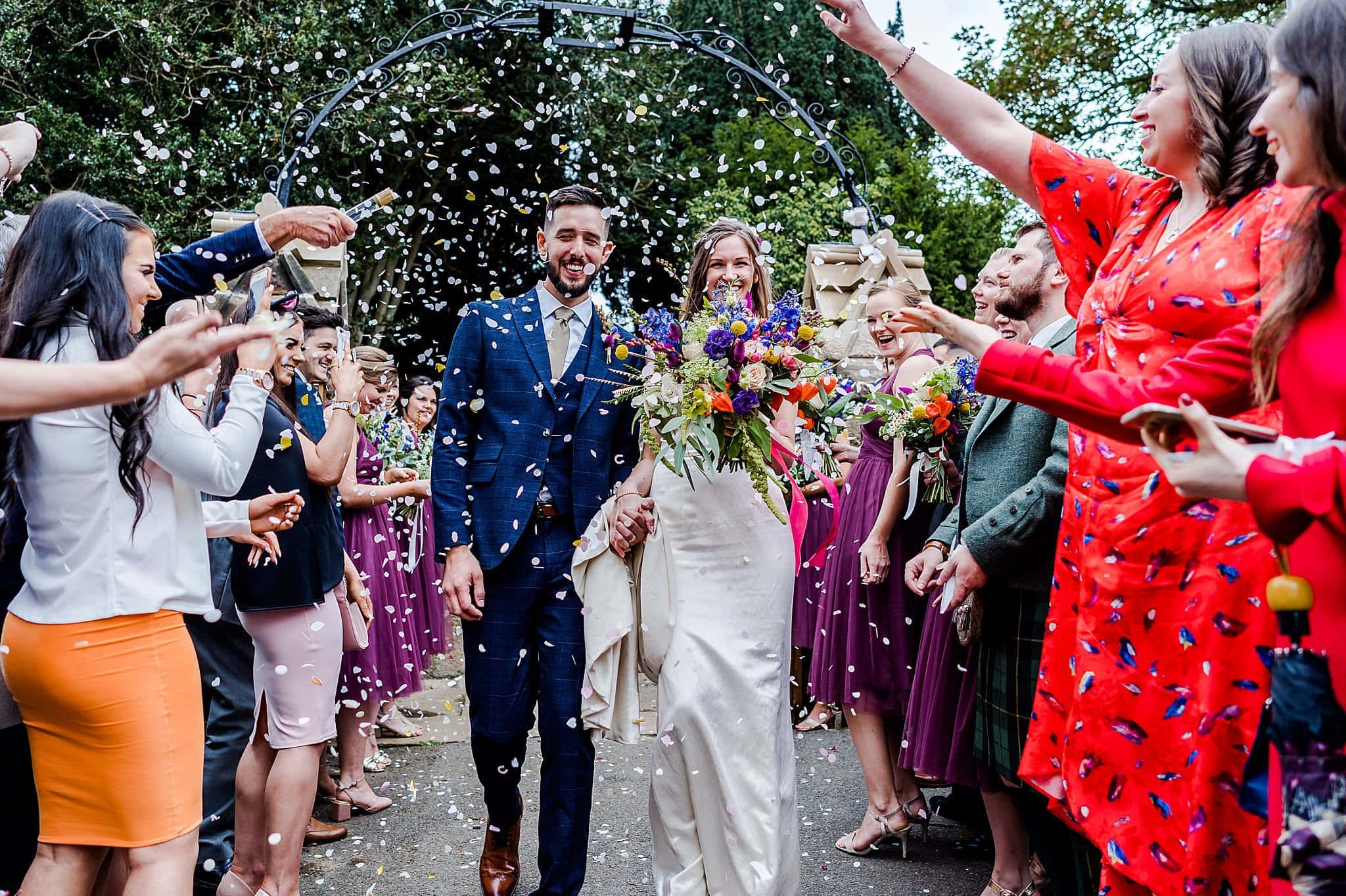 Guests throw confetti over the bride and groom walking away from Rearsby Church