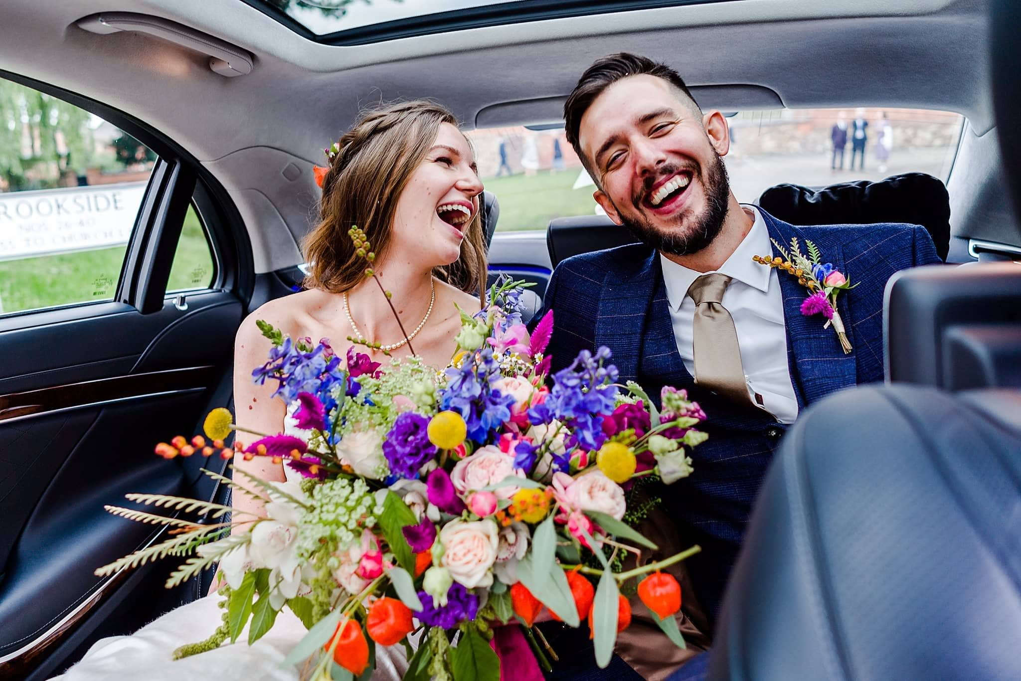 Bride and groom share a big laugh in the back of their wedding car on the way to Prestwold Hall