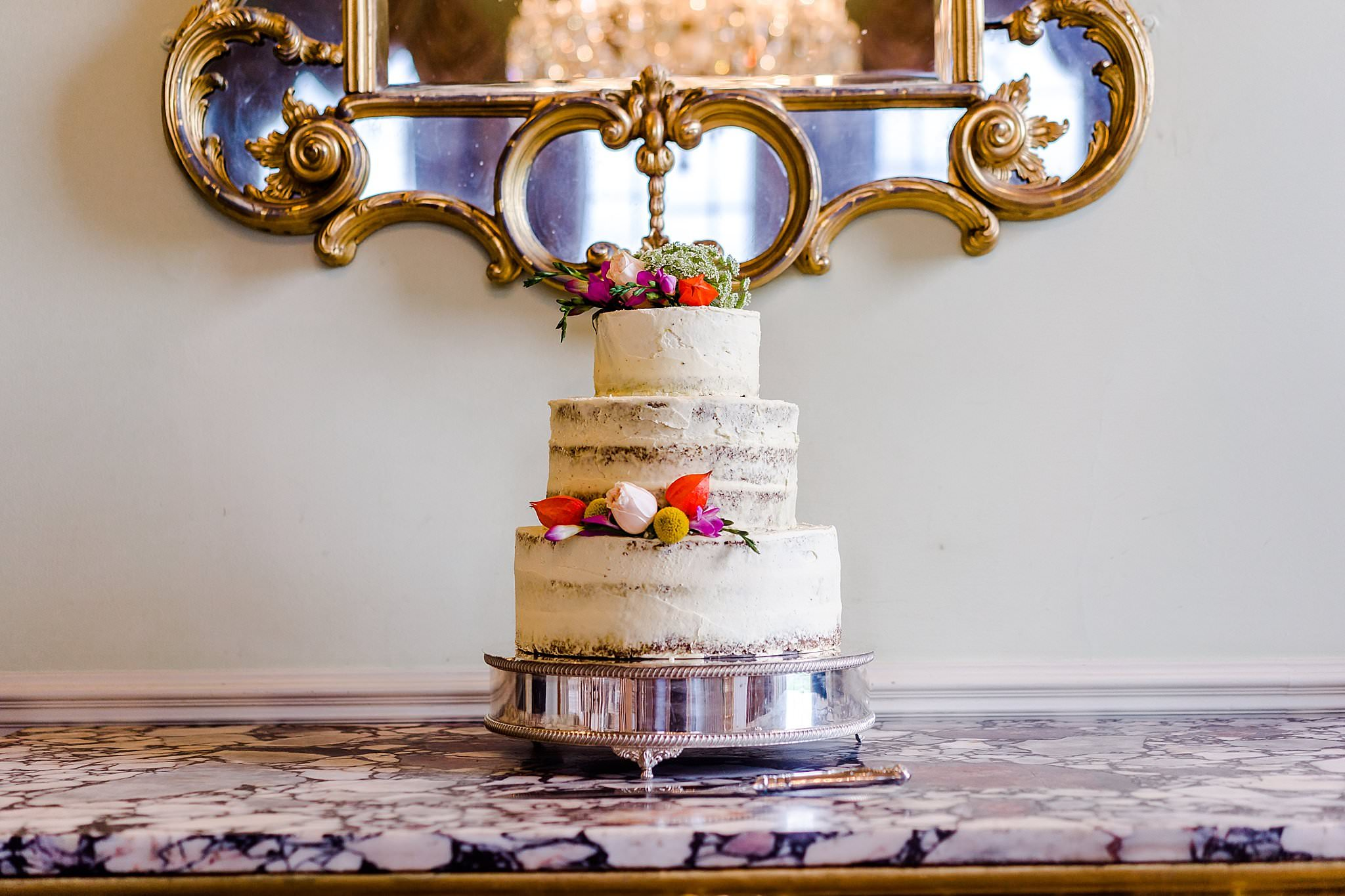 Beautiful semi naked wedding cake on a marble table at Prestwold Hall