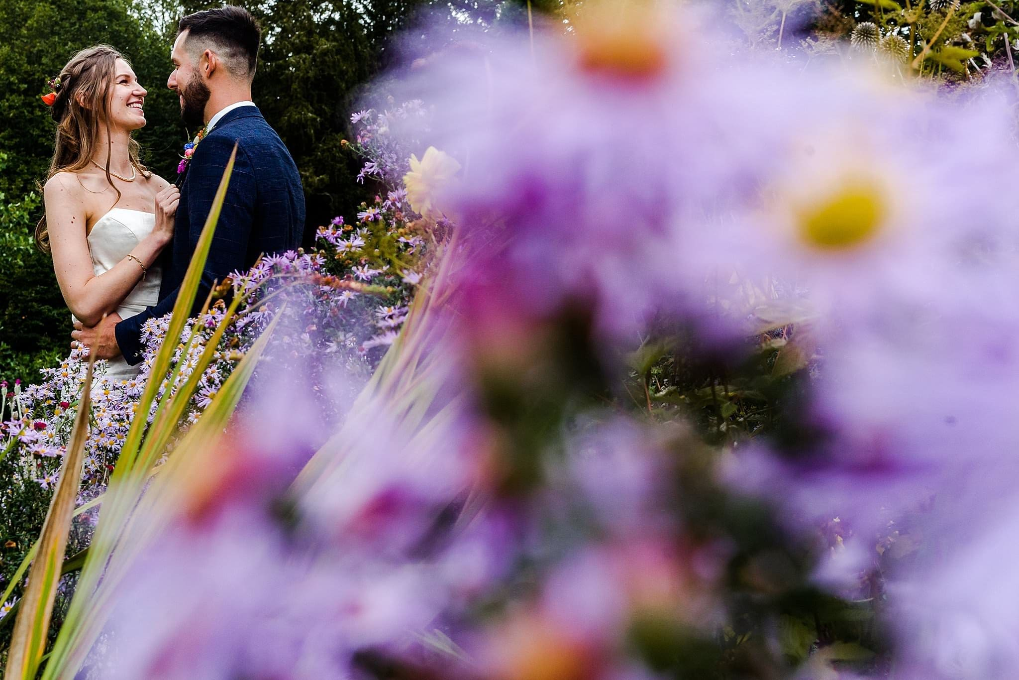 Bride and groom holding each other in the corner of the photo with out of focus colourful flowers in the foreground at Prestwold Hall