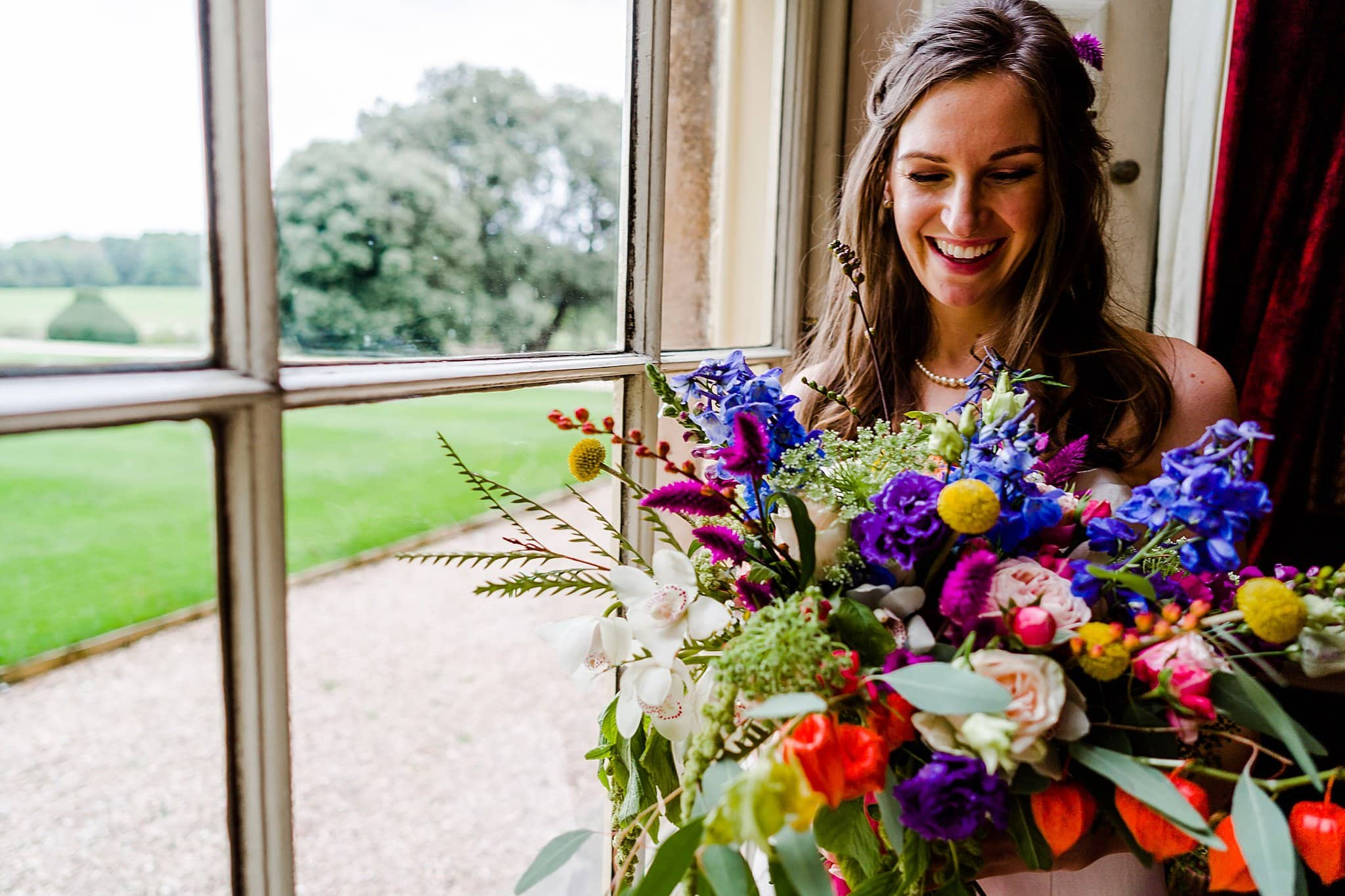 Bride looks at her beautiful colourful flowers whilst stood at the window at Prestwold Hall